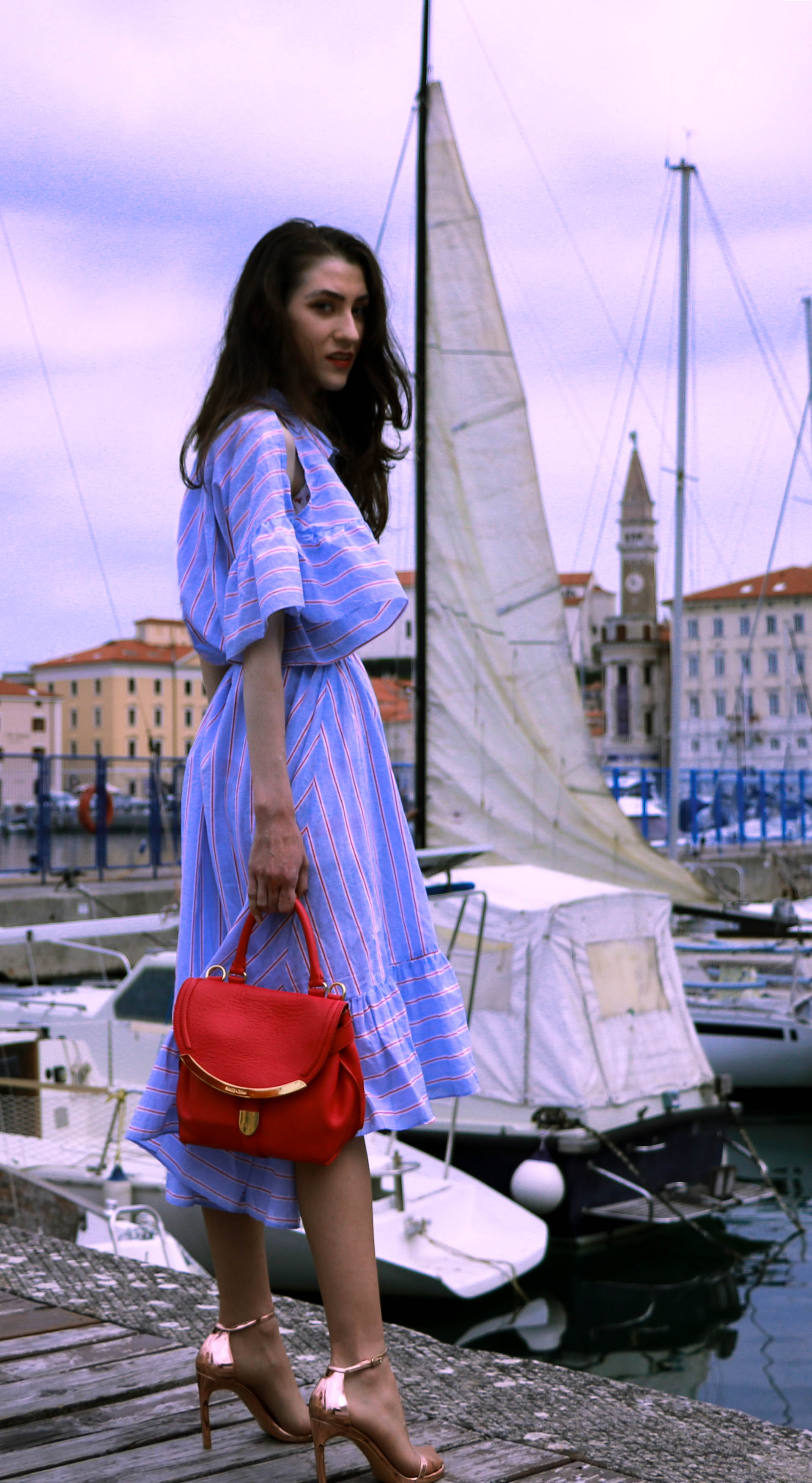 Beautiful Slovenian fashion blogger Veronika Lipar of Brunette from Wall Street wearing striped cold shoulder shirt dress with rope belt Stuart Weitzman nudist song sandals pink See by Chloe top handle bag standing by the sailing boats