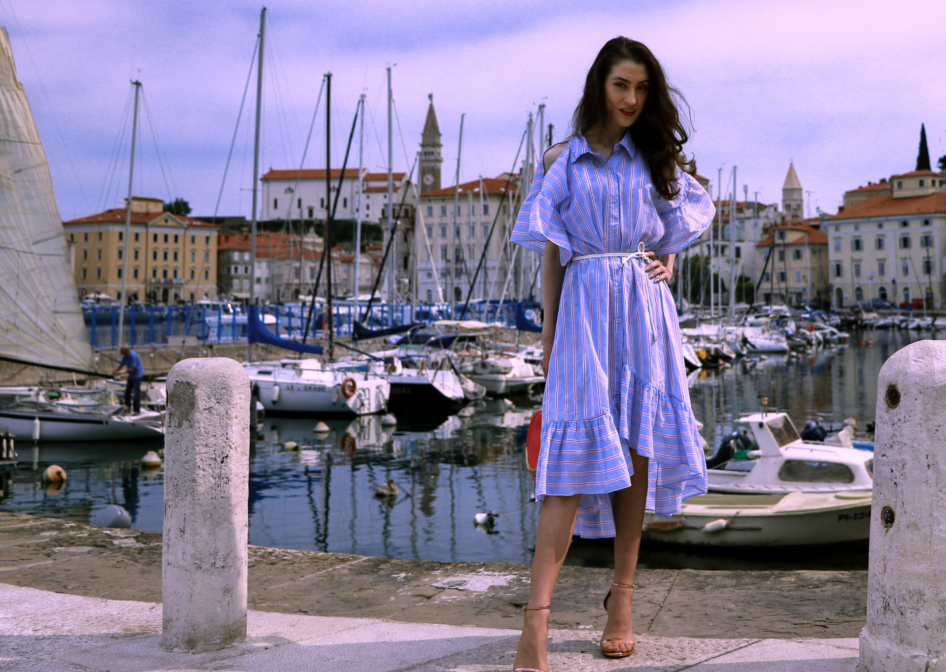 Beautiful Slovenian fashion blogger Veronika Lipar of Brunette from Wall Street wearing striped cold shoulder shirt dress with rope belt Stuart Weitzman nudist song sandals pink See by Chloe top handle bag standing by the boats