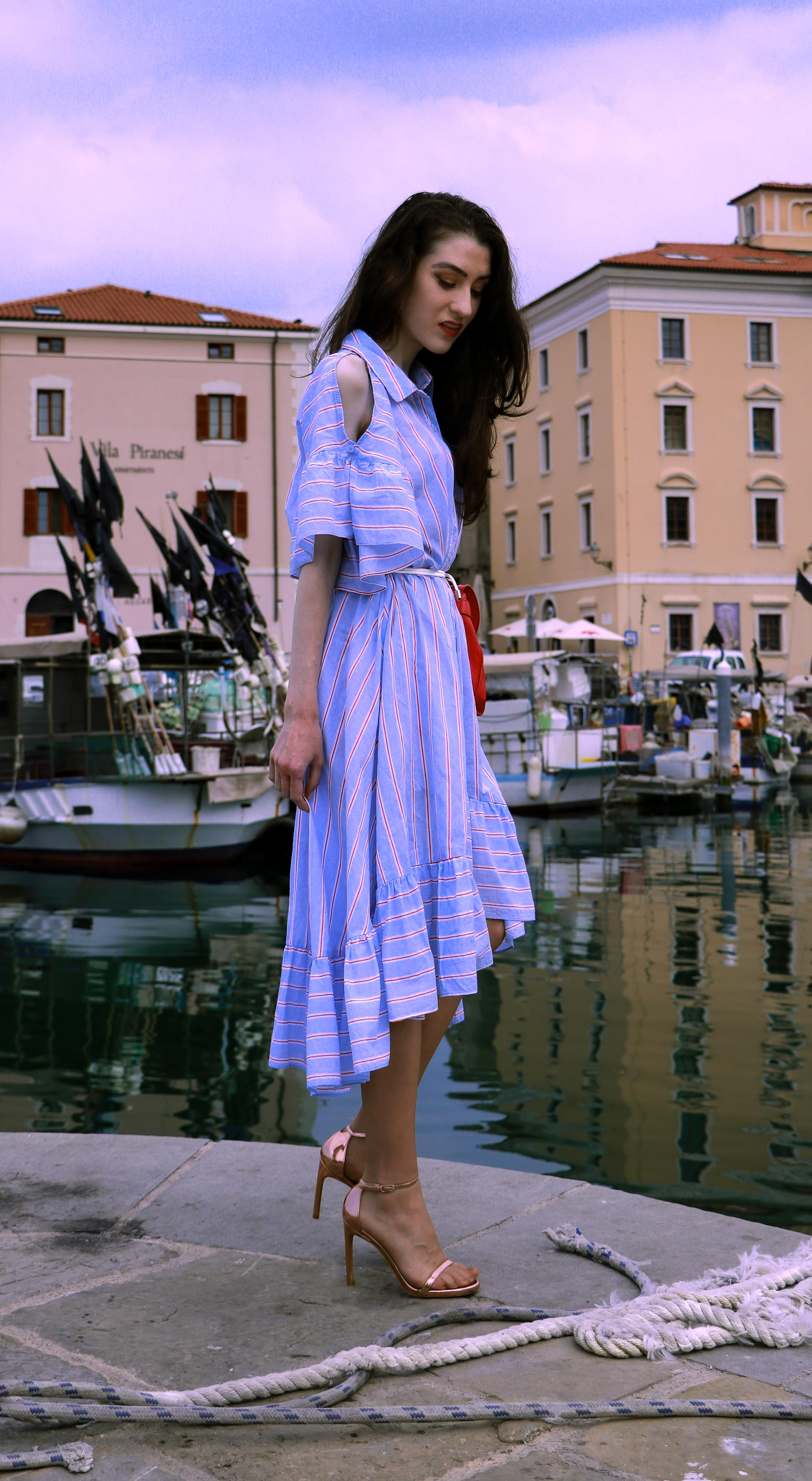 Beautiful Slovenian fashion blogger Veronika Lipar of Brunette from Wall Street wearing striped cold shoulder shirt dress with rope belt Stuart Weitzman nudist song sandals pink See by Chloe top handle bag standing by the sailing rope