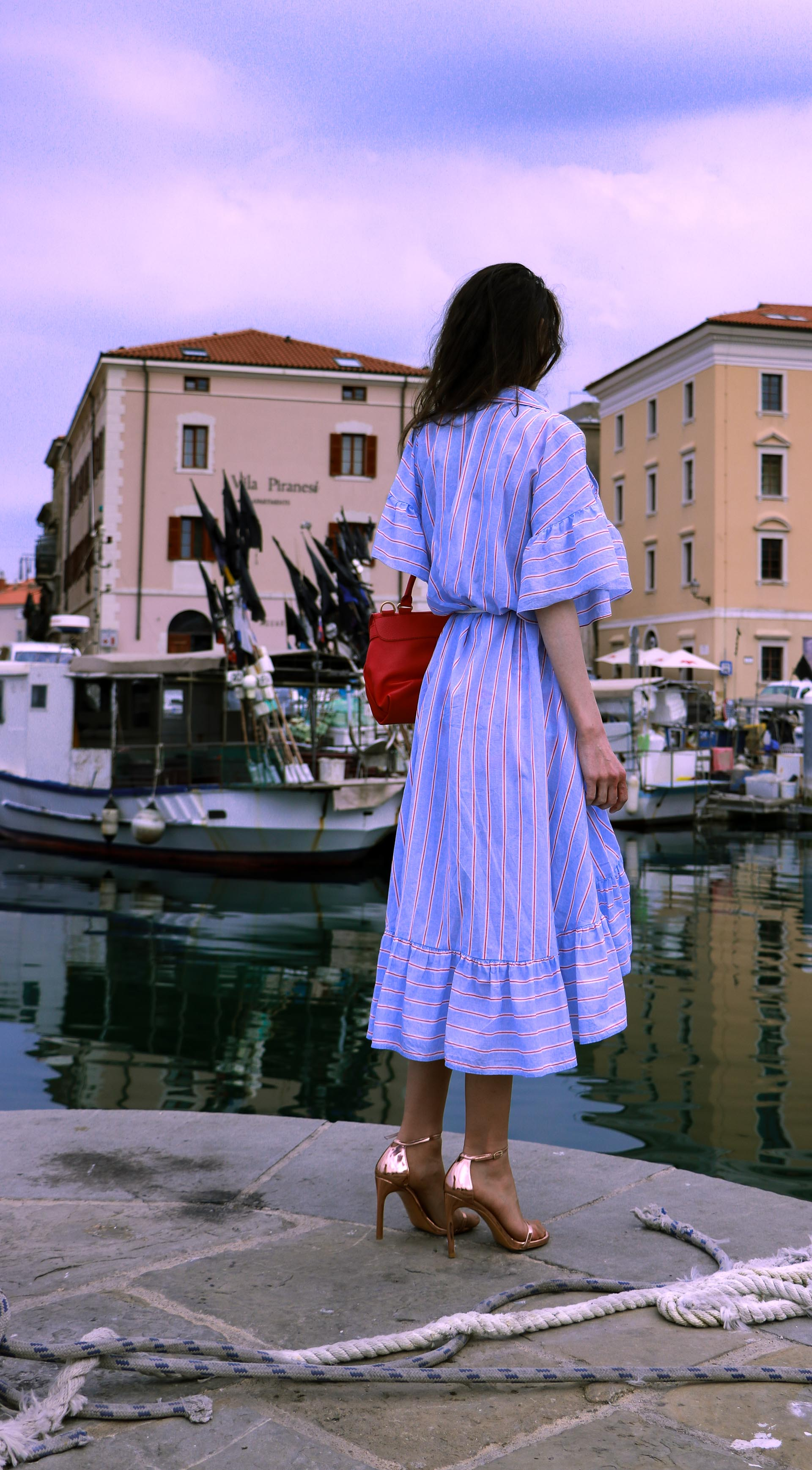 Beautiful Slovenian fashion blogger Veronika Lipar of Brunette from Wall Street dressed in striped cold shoulder shirt dress with rope belt Stuart Weitzman nudist song sandals pink See by Chloe top handle bag standing by the sailing rope