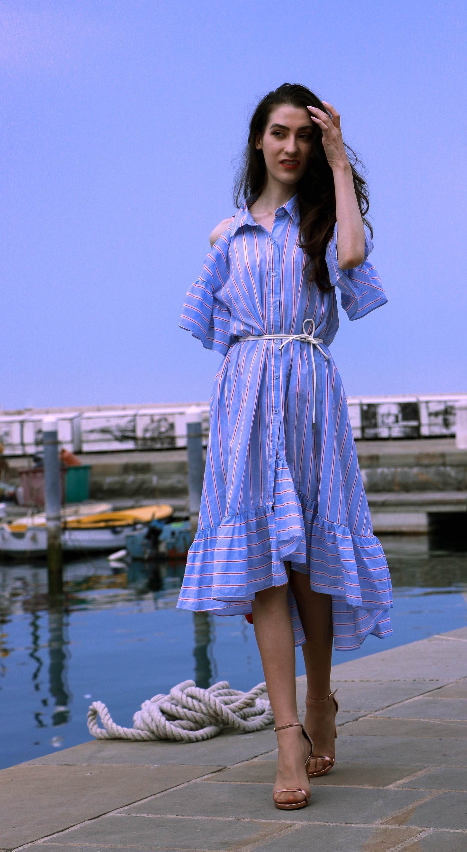 Beautiful Slovenian fashion blogger Veronika Lipar of Brunette from Wall Street dressed in striped cold shoulder shirt dress with rope belt Stuart Weitzman nudist song sandals pink See by Chloe top handle bag standing by the boats