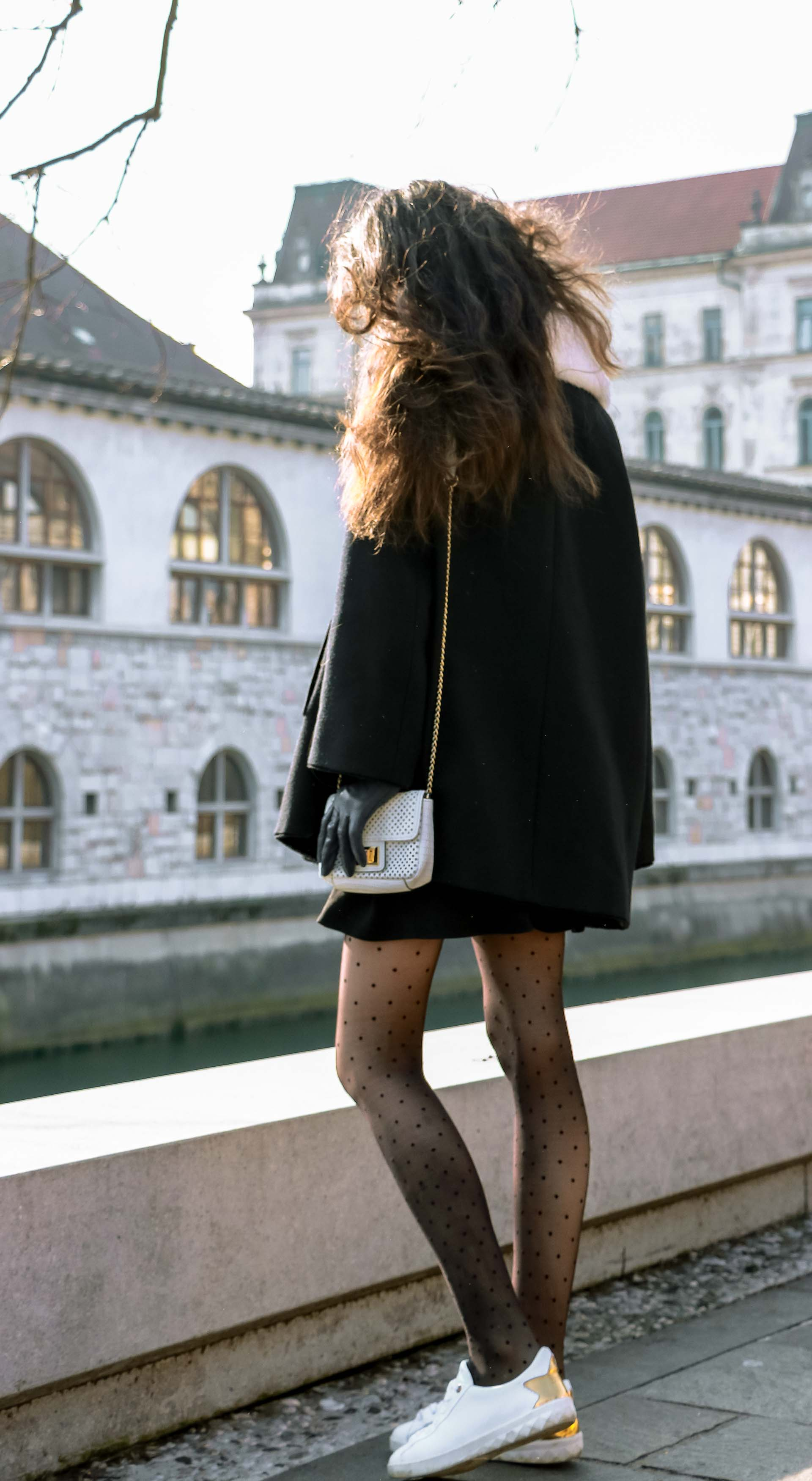 Fashion Blogger Veronika Lipar of Brunette from Wall Street wearing black Escada cape, black mini skirt and white sneakers from Diesel with black polka dot tights and white shoulder chain bag and blue leather gloves