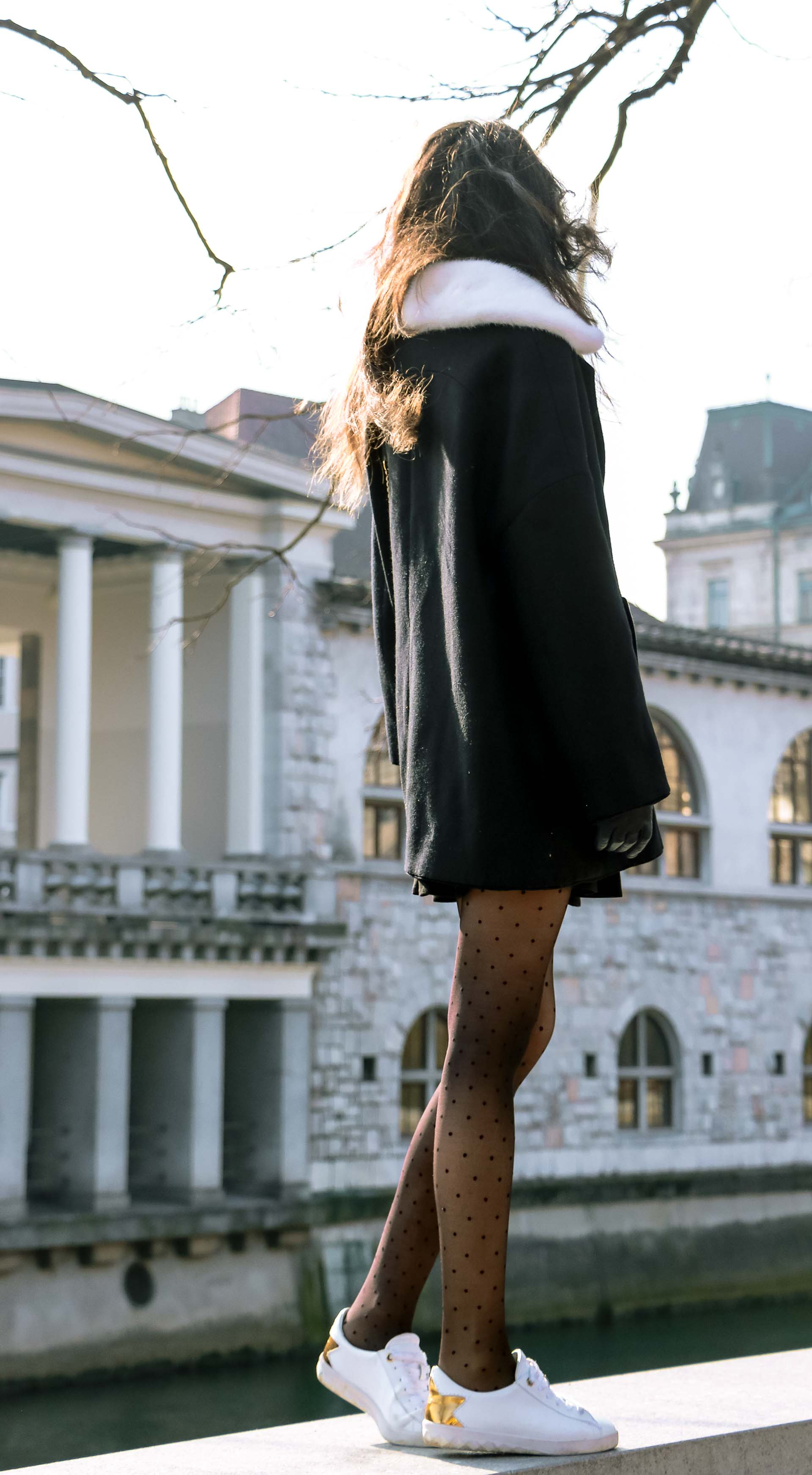 Fashion Blogger Veronika Lipar of Brunette from Wall Street wearing black Escada cape, black mini skirt and white sneakers from Diesel with black polka dot tights and white shoulder chain bag and blue leather gloves while standing on a wall showing her back