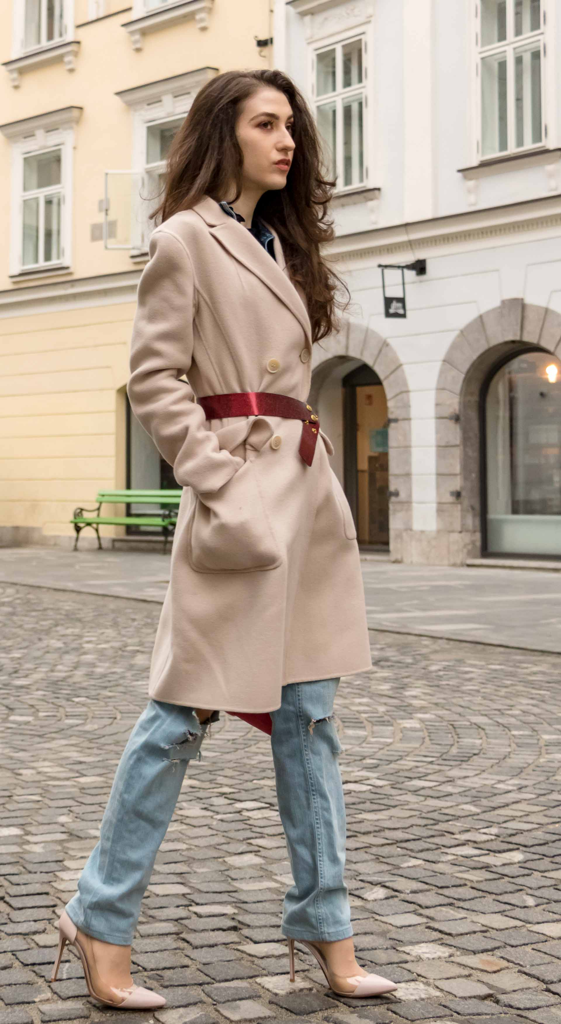 Fashion Blogger Veronika Lipar of Brunette from Wall Street dressed in ripped blue Levi's jeans, off-white double breasted Weekend Maxmara coat, red dangling belt, blush Gianvito Rossi plexi pumps, See by Chloe pink top handle bag, blue leather gloves walking in Ljubljana