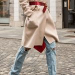 Fashion Blogger Veronika Lipar of Brunette from Wall Street dressed in ripped blue Levi's jeans, off-white double breasted Weekend Maxmara coat, red dangling belt, blush Gianvito Rossi plexi pumps, See by Chloe pink top handle bag, blue leather gloves walking down the street in Ljubljana