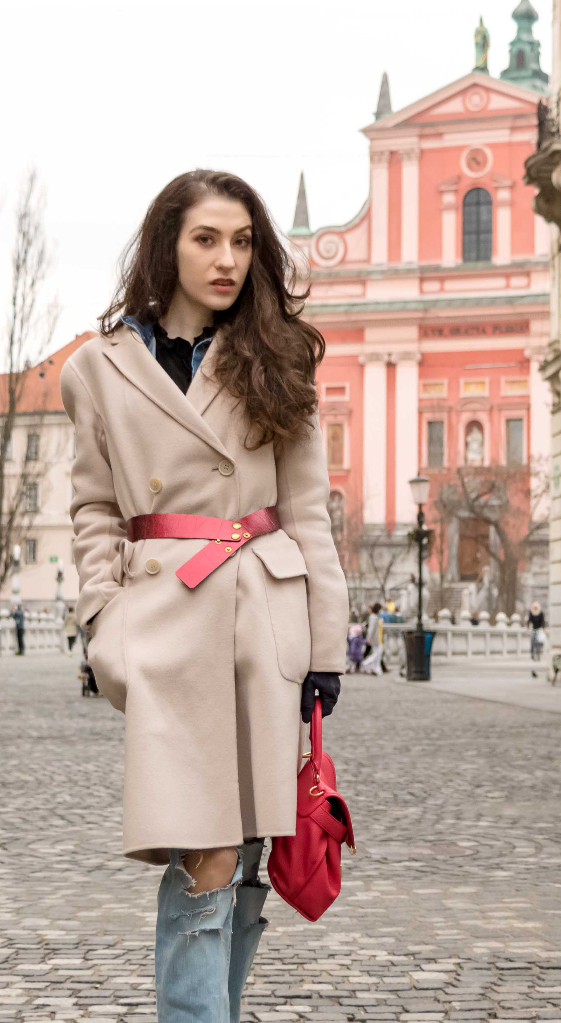 Fashion Blogger Veronika Lipar of Brunette from Wall Street wearing ripped blue Levi's jeans, off-white double breasted Weekend Maxmara coat, red dangling belt, See by Chloe pink top handle bag, blue leather gloves walking down the street in Ljubljana