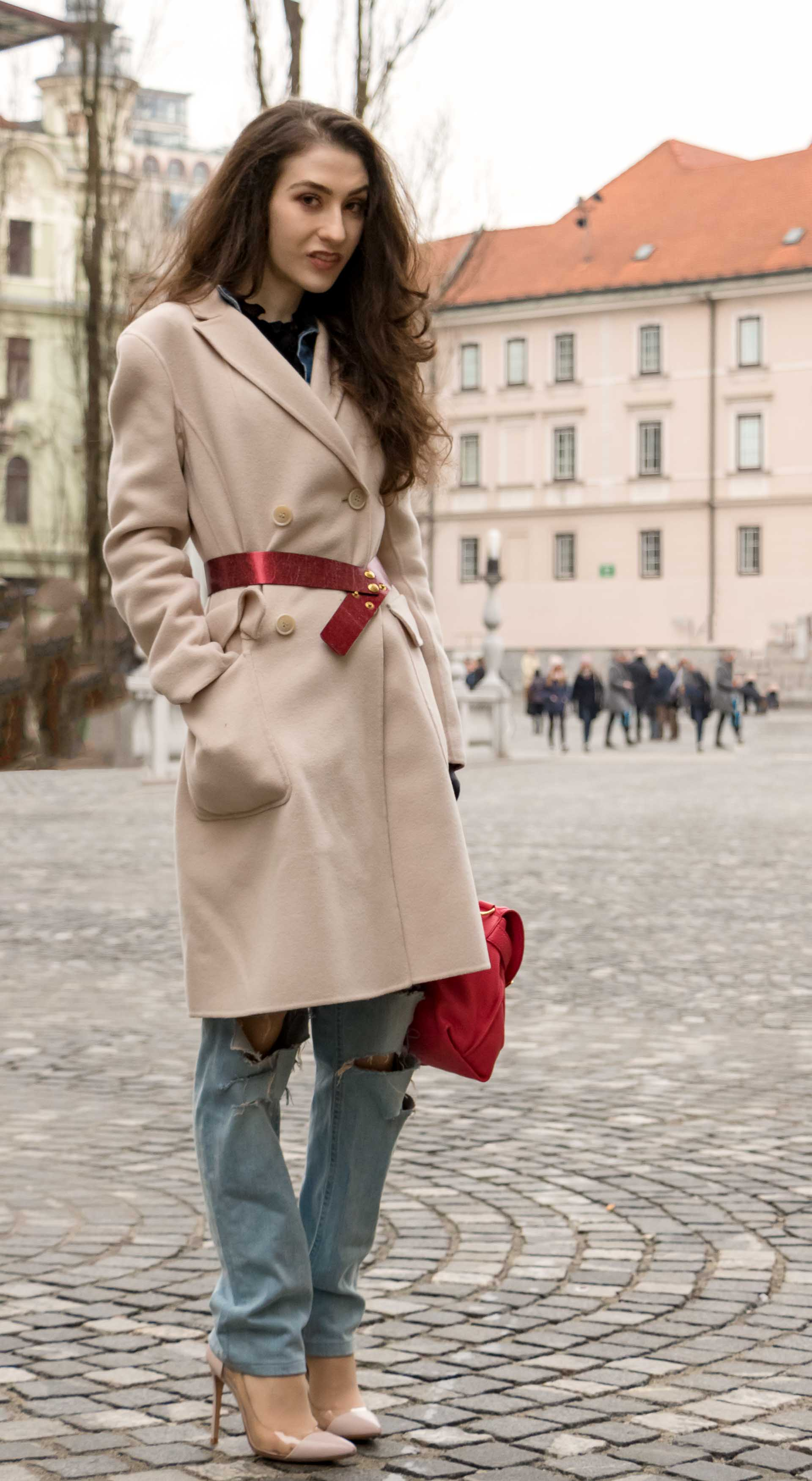 Fashion Blogger Veronika Lipar of Brunette from Wall Street dressed in ripped blue Levi's jeans, off-white double breasted Weekend Maxmara coat, red dangling belt, blush Gianvito Rossi plexi pumps, See by Chloe pink top handle bag, blue leather gloves on the street of Ljubljana