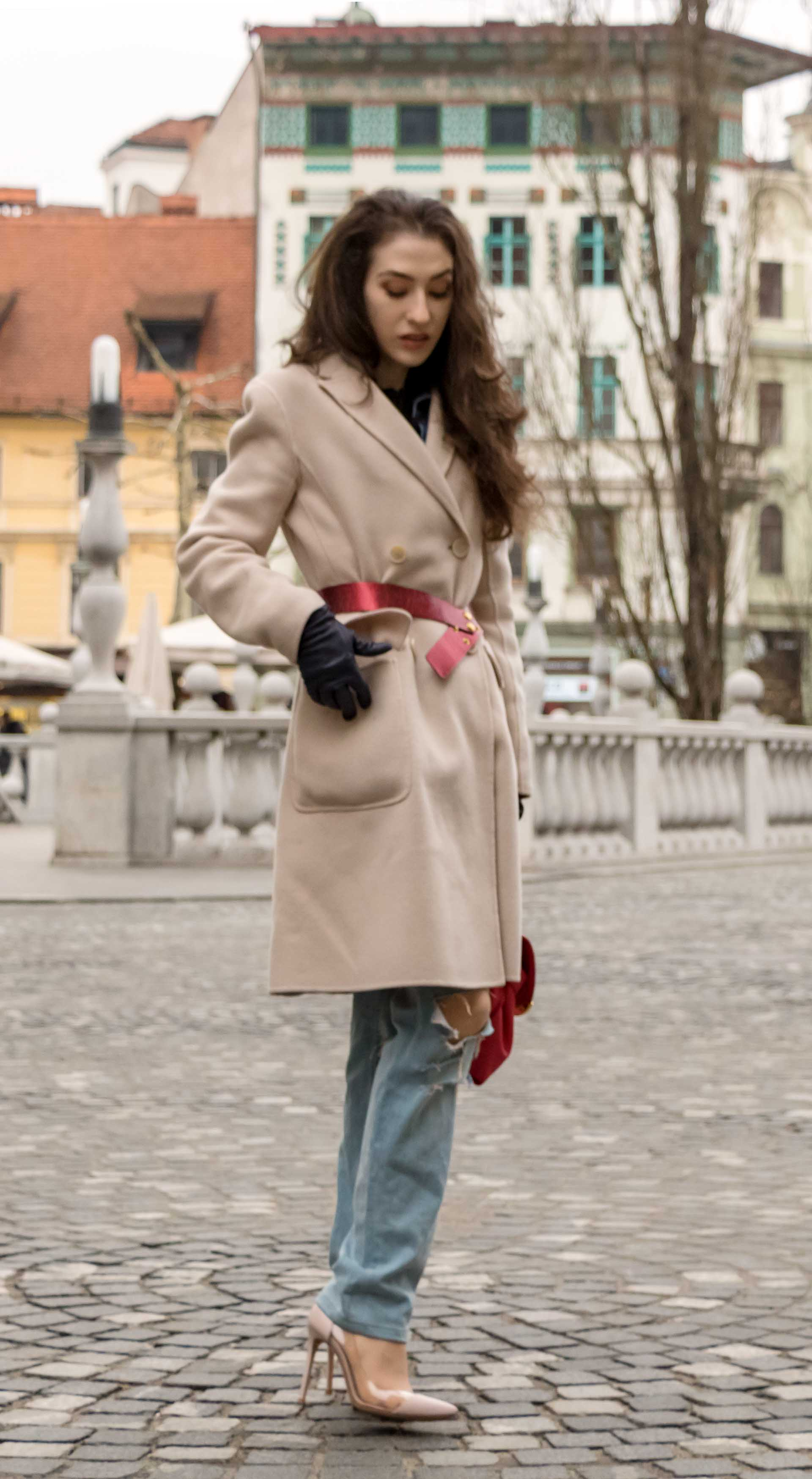Fashion Blogger Veronika Lipar of Brunette from Wall Street dressed in distressed blue Levi's jeans, off-white double breasted Weekend Maxmara coat, red dangling belt, blush Gianvito Rossi plexi pumps, See by Chloe pink top handle bag, blue leather gloves reaching her pocket
