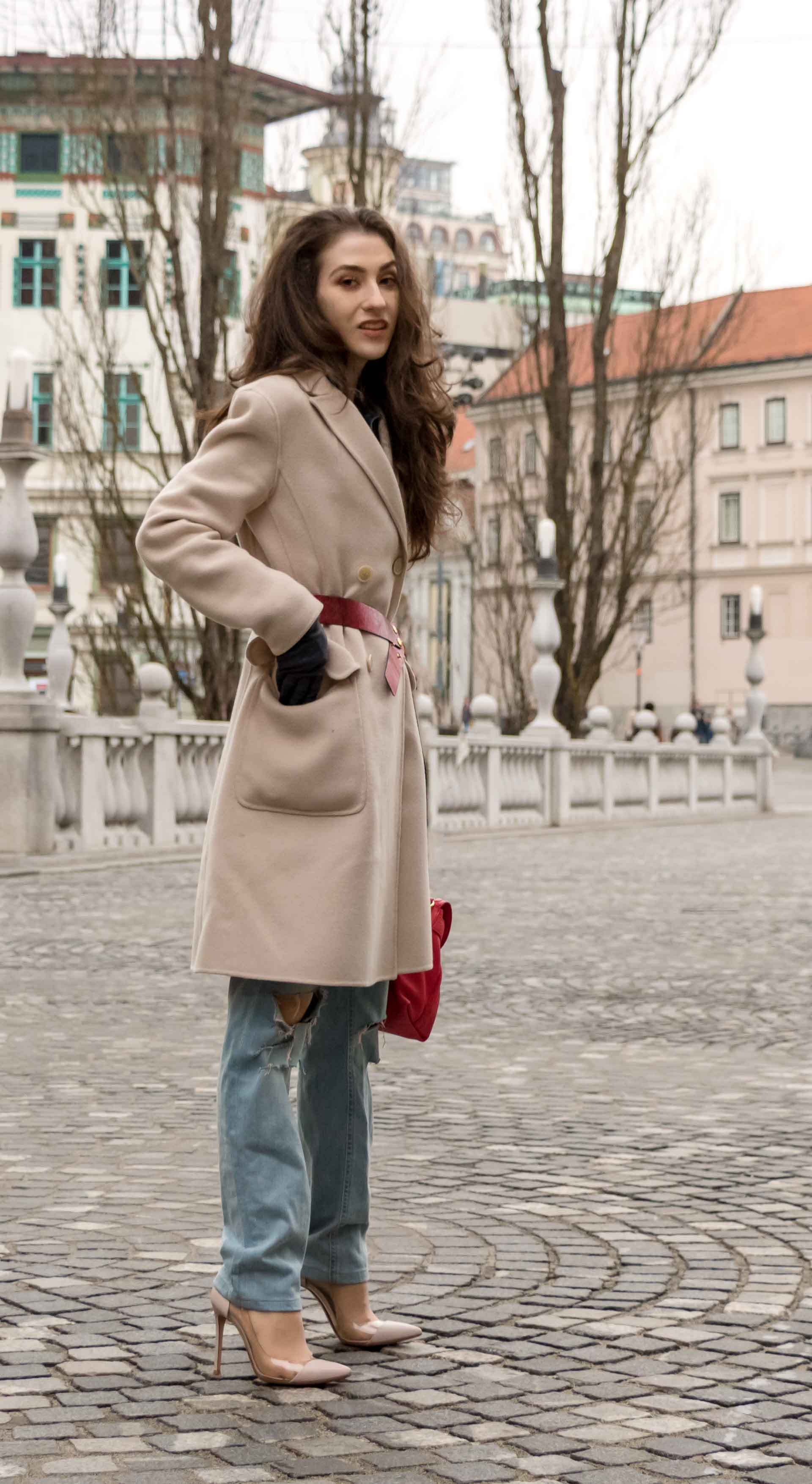 Fashion Blogger Veronika Lipar of Brunette from Wall Street wearing ripped blue Levi's jeans, off-white double breasted Weekend Maxmara coat, red dangling belt, blush Gianvito Rossi plexi pumps, See by Chloe pink top handle bag, blue leather putting hand in the coat's pocket