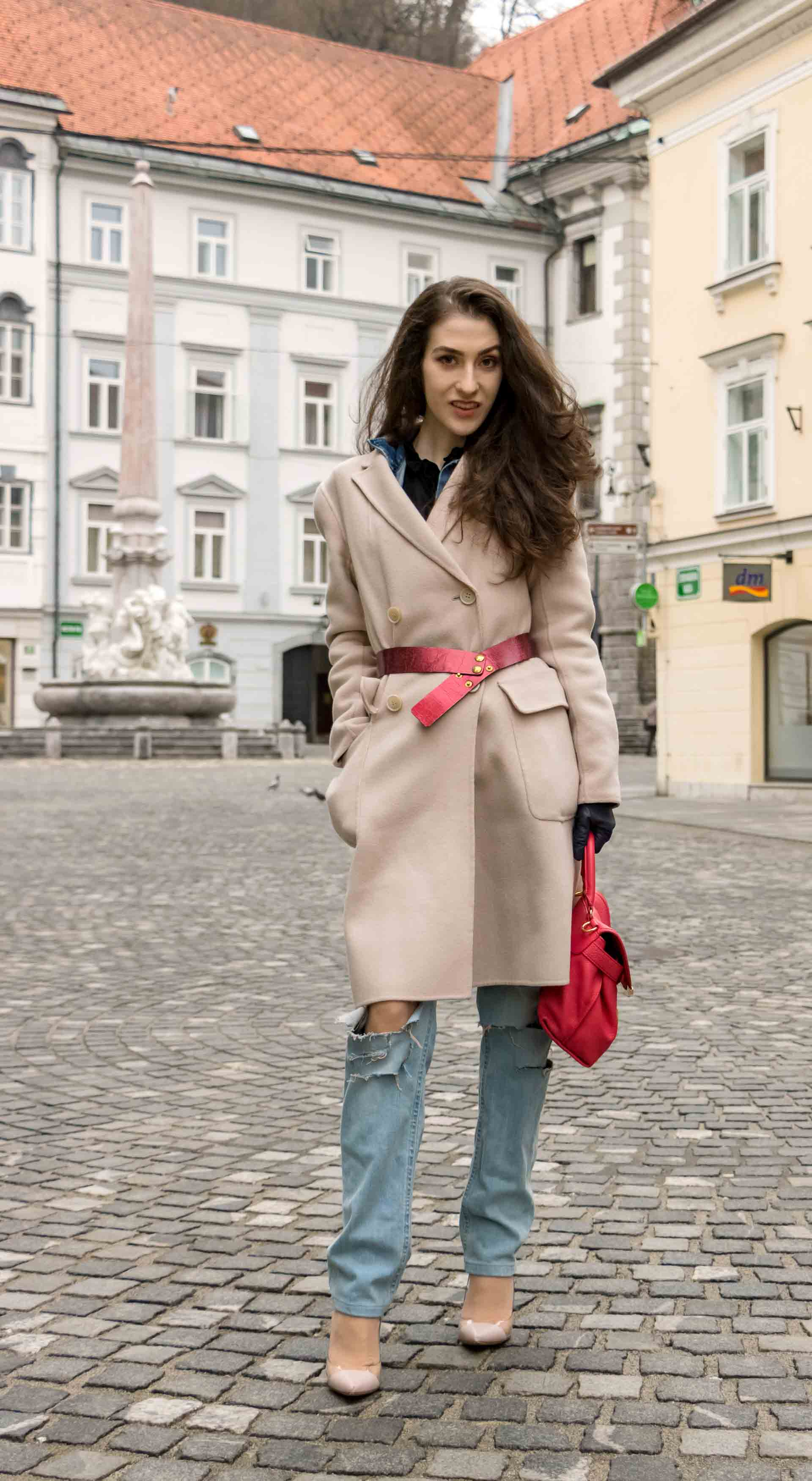 Fashion Blogger Veronika Lipar of Brunette from Wall Street dressed in ripped blue Levi's jeans, off-white double breasted Weekend Maxmara coat, red dangling belt, blush Gianvito Rossi plexi pumps, See by Chloe pink top handle bag, blue leather gloves standing on the street of Ljubljana