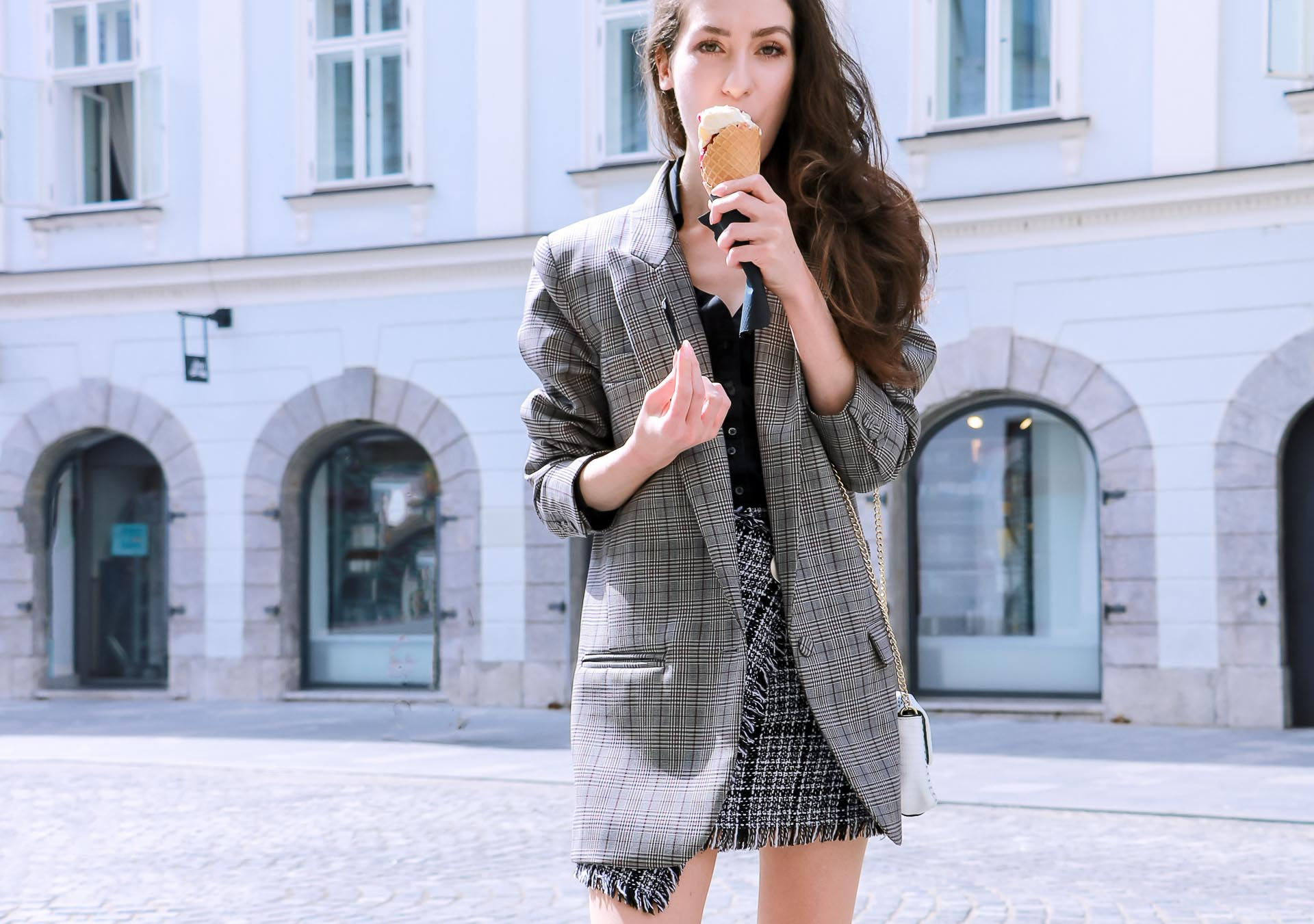 Fashion Blogger Veronika Lipar of Brunette from Wall Street wearing Erika Cavallini oversized boyfriend checked blazer with short tweed black and white mini skirt from streets, and white chain strap shoulder bag while eating ice cream