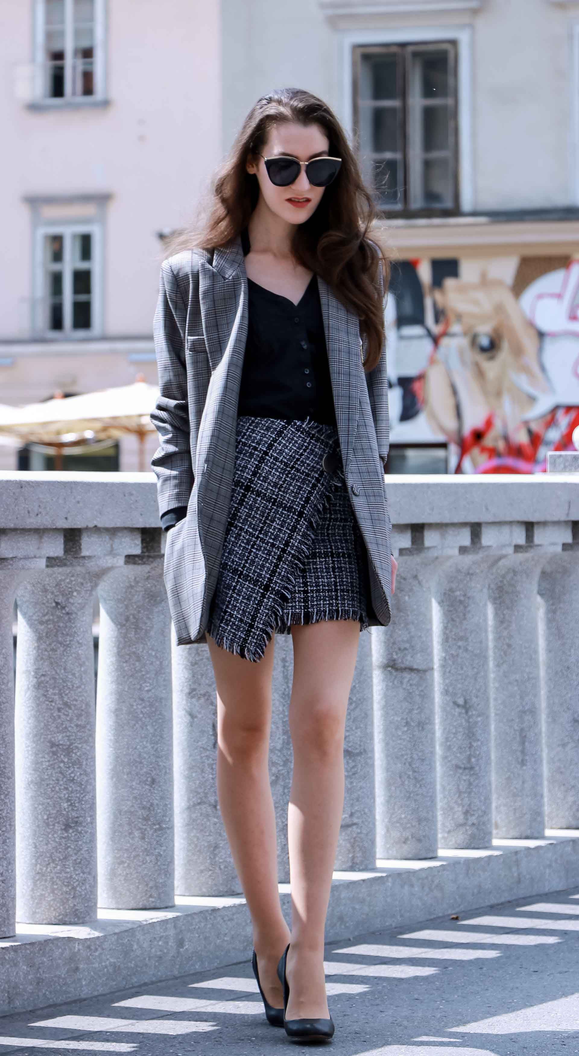 Fashion Blogger Veronika Lipar of Brunette from Wall Street wearing Erika Cavallini oversized boyfriend plaid blazer with short tweed black and white mini skirt from streets, Le specs sunglasses, black pumps and white chain strap shoulder bag while walking down the street in Ljubljana
