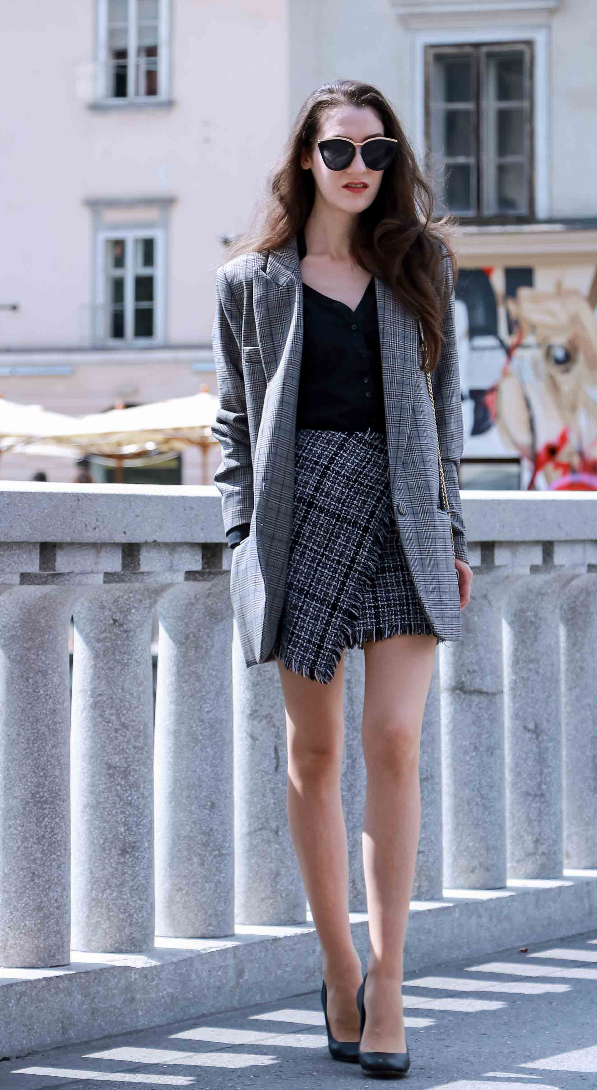 Fashion Blogger Veronika Lipar of Brunette from Wall Street dressed in Erika Cavallini oversized boyfriend plaid blazer with short tweed black and white mini skirt from streets, Le specs sunglasses, black pumps and white chain strap shoulder bag while walking down the street in Ljubljana