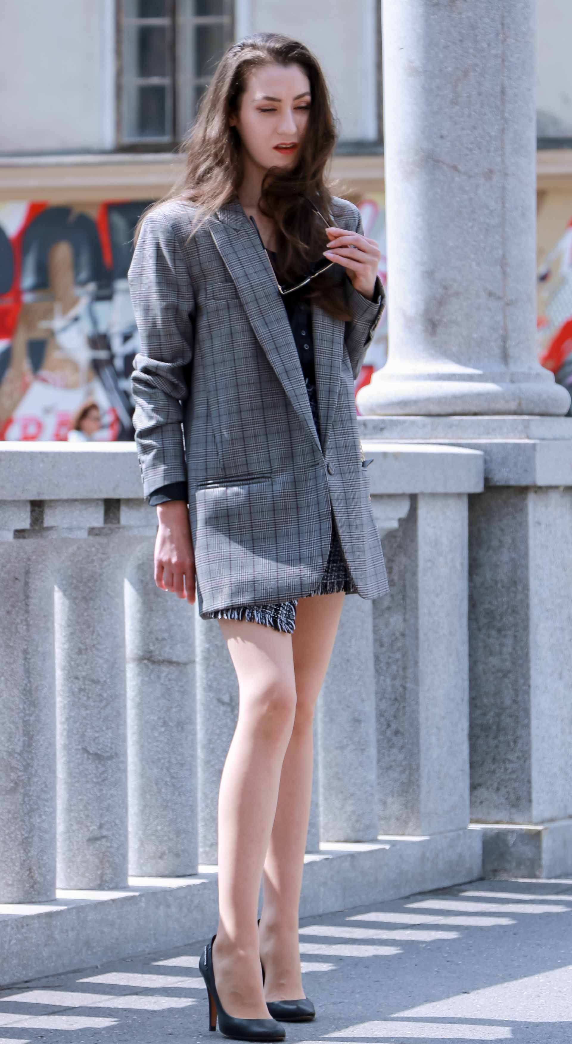 Fashion Blogger Veronika Lipar of Brunette from Wall Street wearing Erika Cavallini oversized boyfriend plaid blazer with short tweed black and white mini skirt from streets, black pumps and white chain strap shoulder bag while standing down the street in Ljubljana