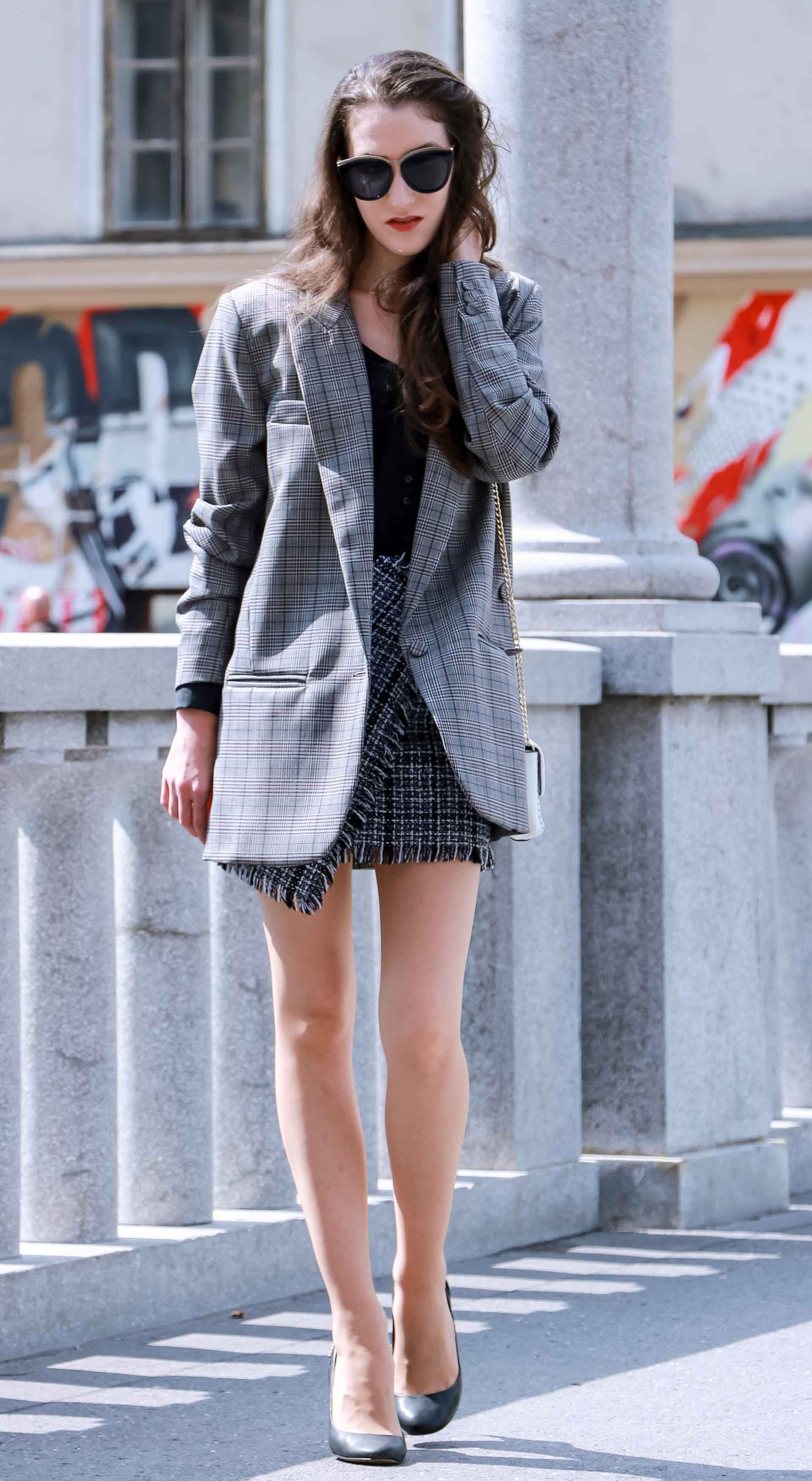 Fashion Blogger Veronika Lipar of Brunette from Wall Street dressed in Erika Cavallini oversized boyfriend checked blazer with short tweed black and white mini skirt from streets, black pumps and white chain strap shoulder bag while walking down the street in Ljubljana