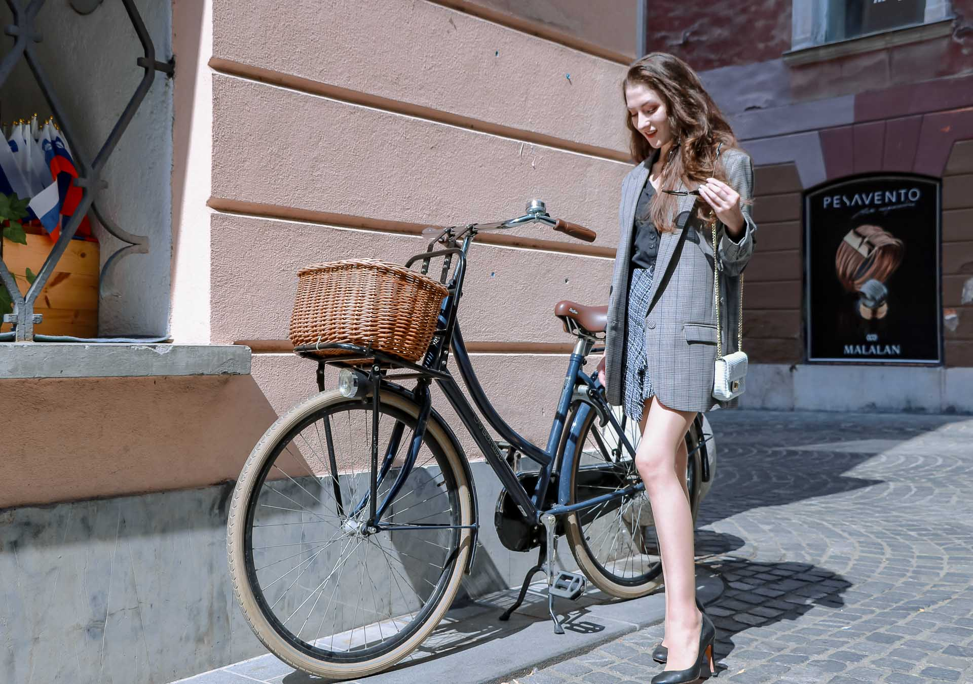 Fashion Blogger Veronika Lipar of Brunette from Wall Street wearing Erika Cavallini oversized boyfriend plaid blazer with short tweed black and white mini skirt from streets, black pumps and white chain strap shoulder bag while standing by the bicycle