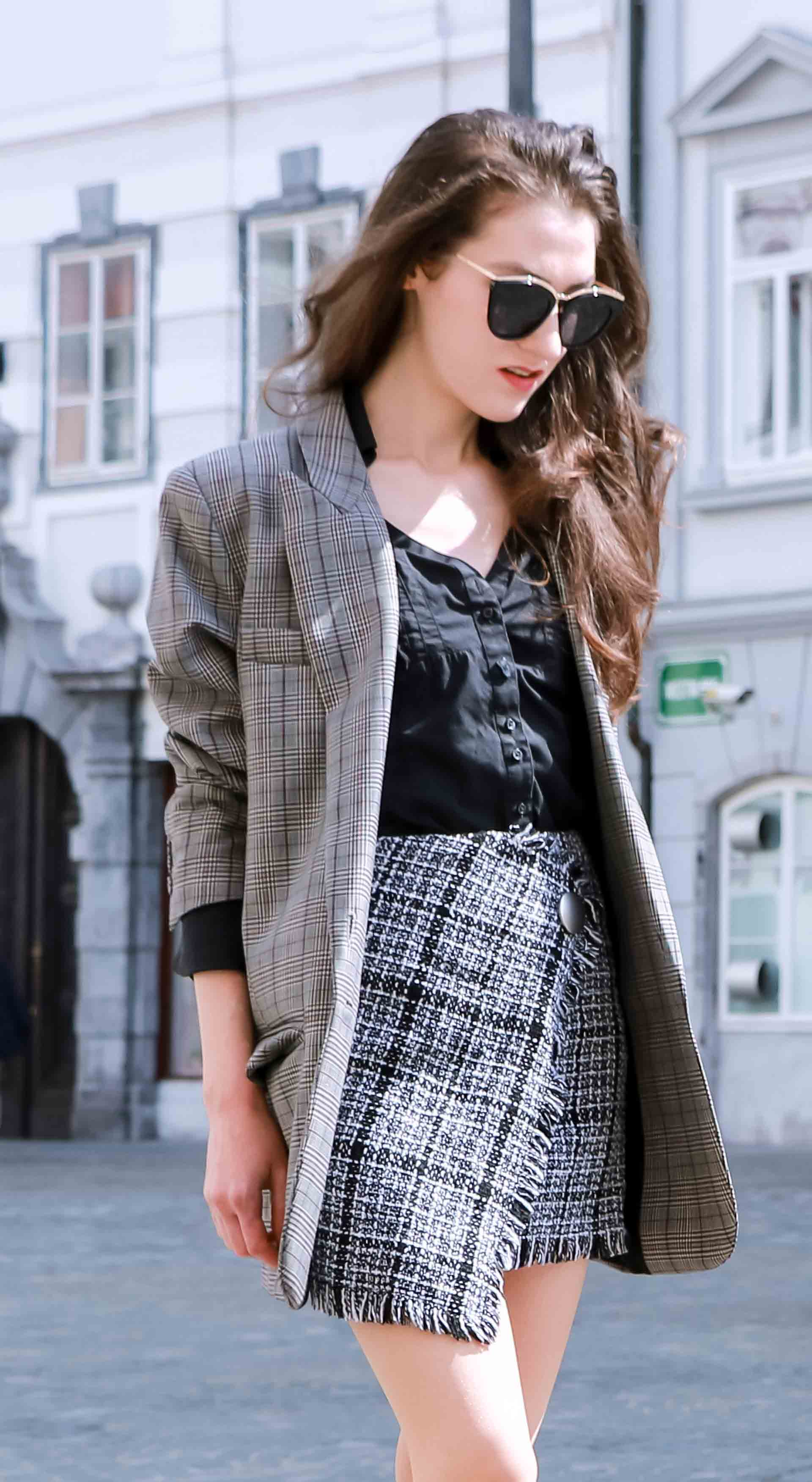 Fashion Blogger Veronika Lipar of Brunette from Wall Street wearing Erika Cavallini oversized boyfriend plaid blazer with short tweed black and white mini skirt from streets, and white chain strap shoulder bag while on the street in Ljubljana