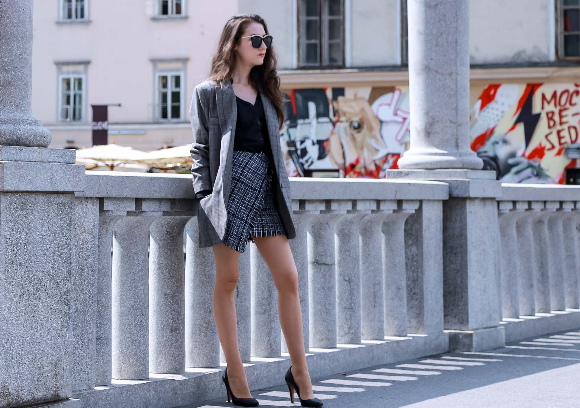 Fashion Blogger Veronika Lipar of Brunette from Wall Street wearing Erika Cavallini oversized boyfriend plaid blazer with short tweed black and white mini skirt from streets, black pumps and white chain strap shoulder bag while standing on the bridge in Ljubljana