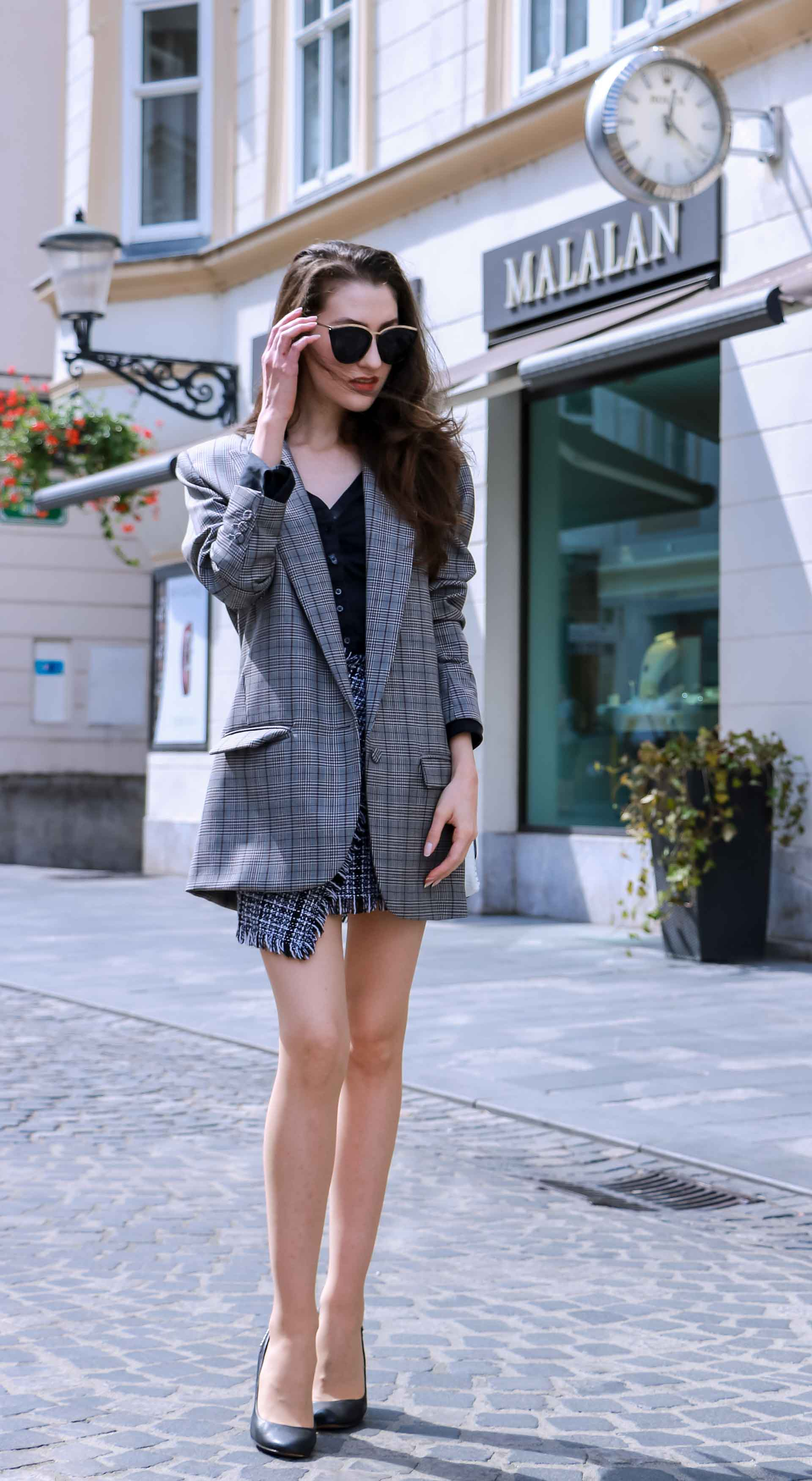 Fashion Blogger Veronika Lipar of Brunette from Wall Street dressed in Erika Cavallini oversized boyfriend plaid blazer with short tweed black and white mini skirt from streets, black pumps and white chain strap shoulder bag while standing down the street in Ljubljana