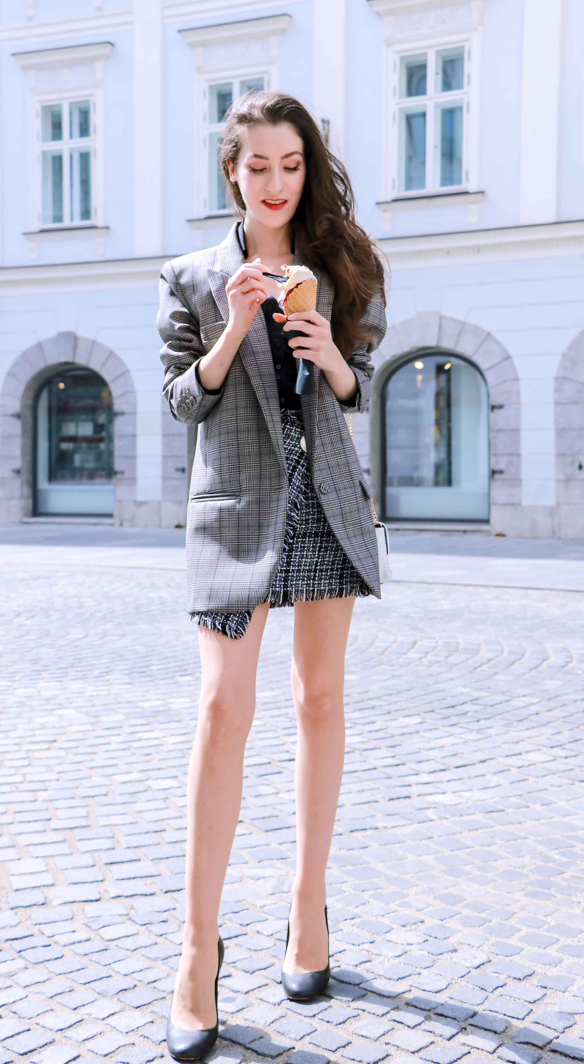 Fashion Blogger Veronika Lipar of Brunette from Wall Street wearing Erika Cavallini oversized boyfriend plaid blazer with short tweed black and white mini skirt from streets, black pumps and white chain strap shoulder bag while eating ice cream