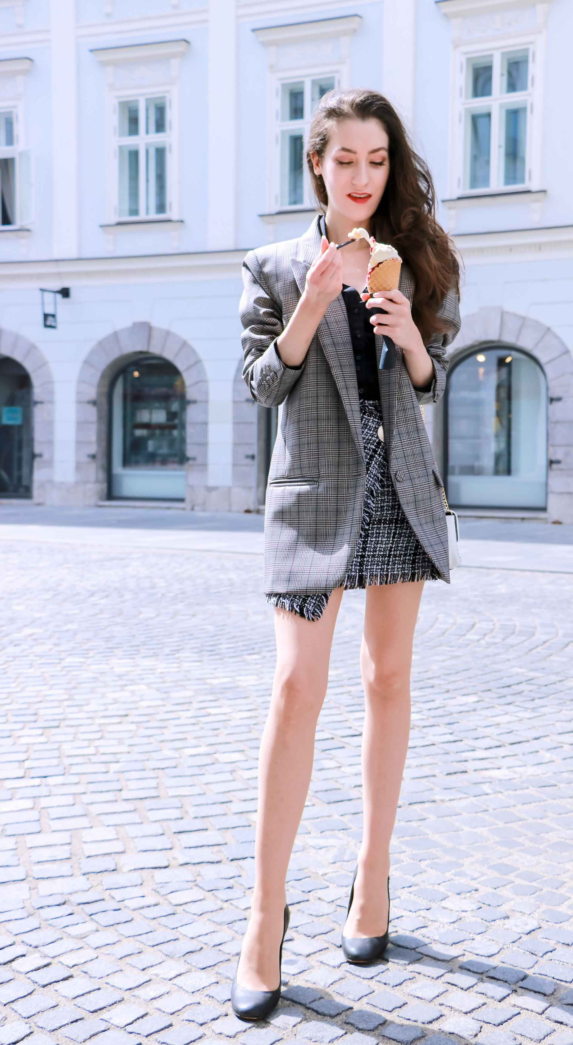 Fashion Blogger Veronika Lipar of Brunette from Wall Street dressed in Erika Cavallini oversized boyfriend plaid blazer with short tweed black and white mini skirt from streets, black pumps and white chain strap shoulder bag while eating ice cream in sugar cone