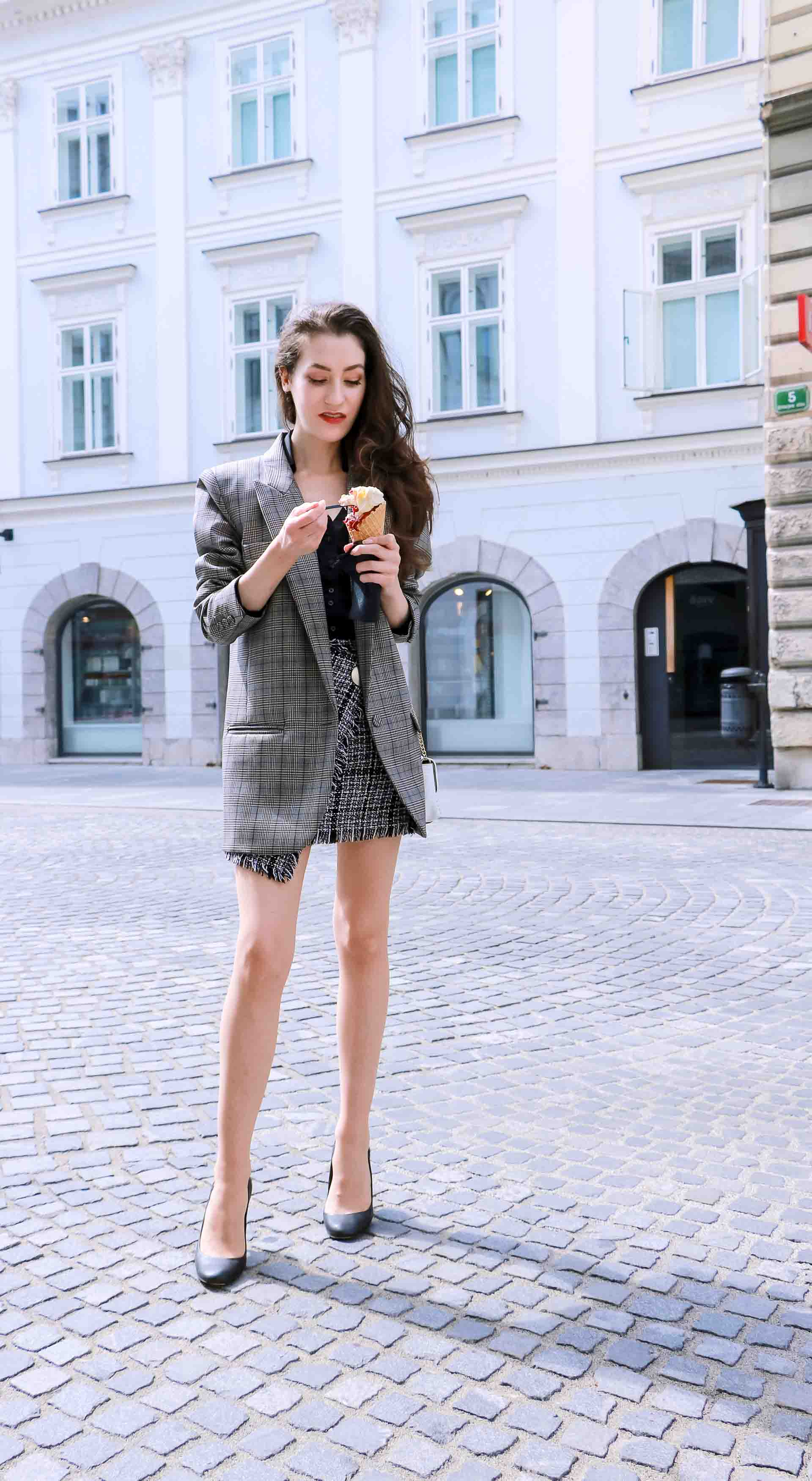 Fashion Blogger Veronika Lipar of Brunette from Wall Street dressed in Erika Cavallini oversized boyfriend checked blazer with short tweed black and white mini skirt from streets, black pumps and white chain strap shoulder bag while eating ice cream in sugar cone