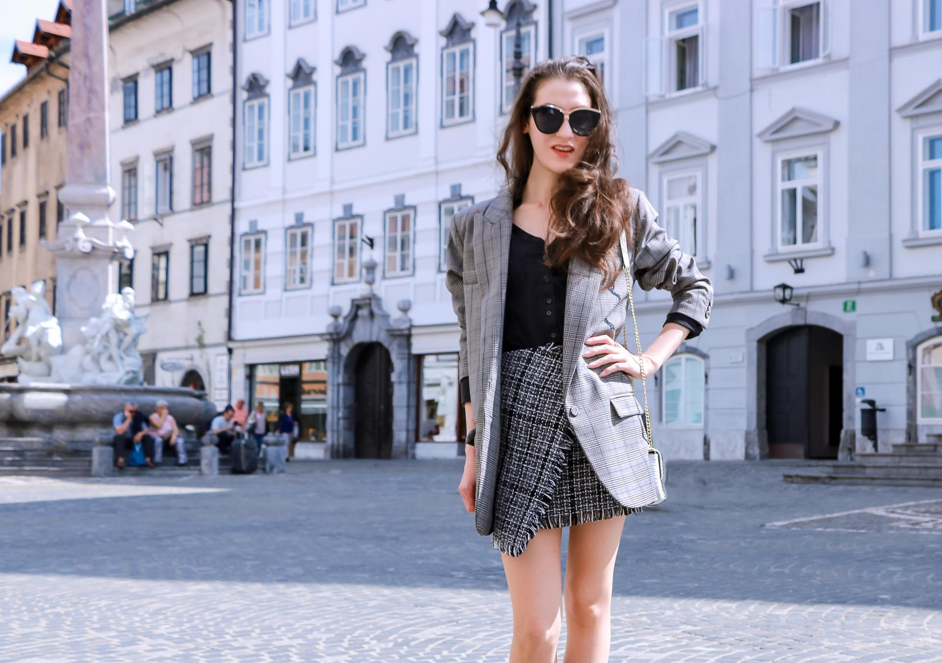 Fashion Blogger Veronika Lipar of Brunette from Wall Street dressed in Erika Cavallini oversized boyfriend plaid blazer with short tweed black and white mini skirt from streets, and white chain strap shoulder bag while on the street in Ljubljana