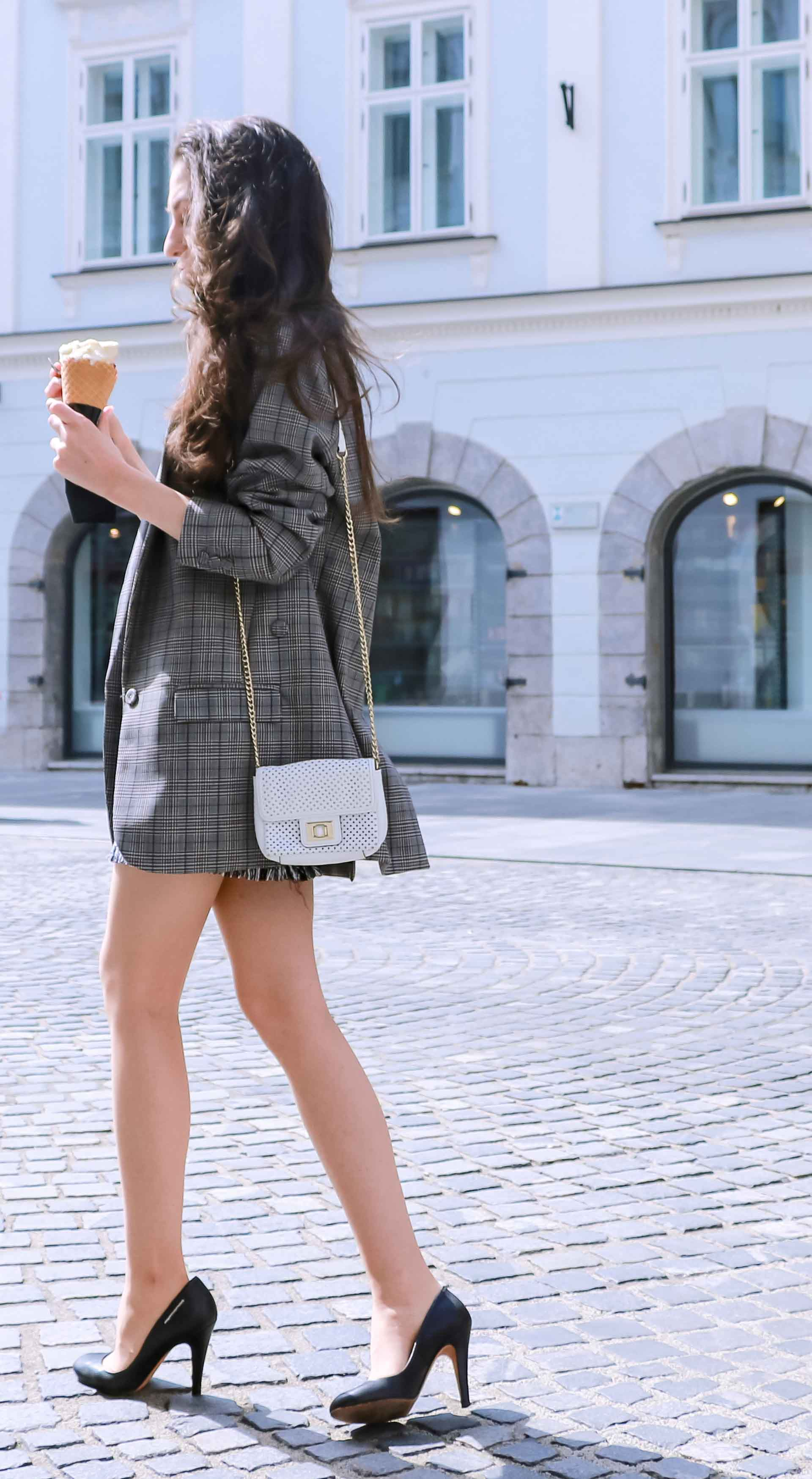 Fashion Blogger Veronika Lipar of Brunette from Wall Street wearing Erika Cavallini oversized boyfriend plaid blazer with short tweed black and white mini skirt from streets, black pumps and white chain strap shoulder bag while walking down the street in Ljubljana with ice cream in her hand