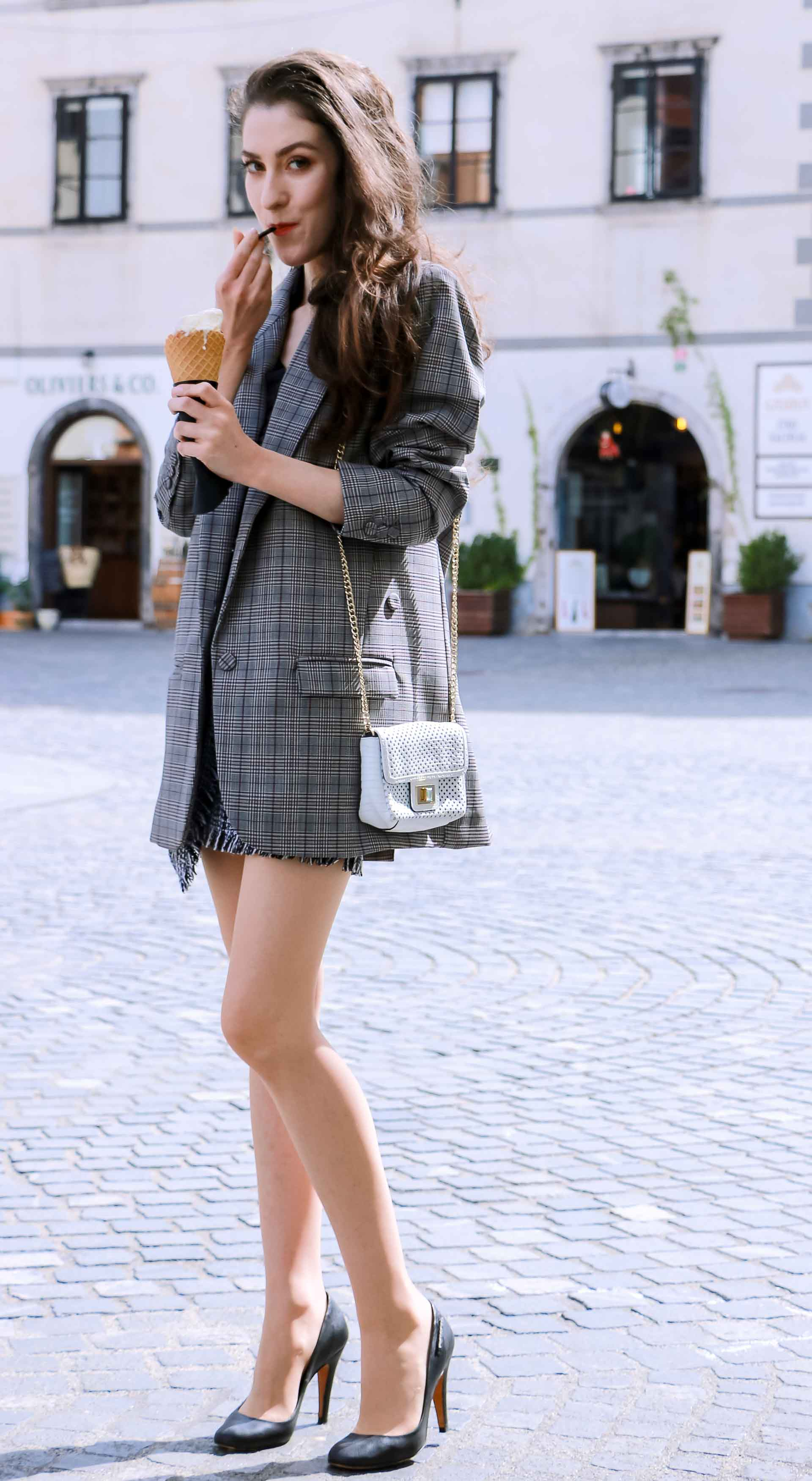 Fashion Blogger Veronika Lipar of Brunette from Wall Street wearing Erika Cavallini oversized boyfriend checked blazer with short tweed black and white mini skirt from streets, black pumps and white chain strap shoulder bag while standing down the street in Ljubljana with ice cream in her hand