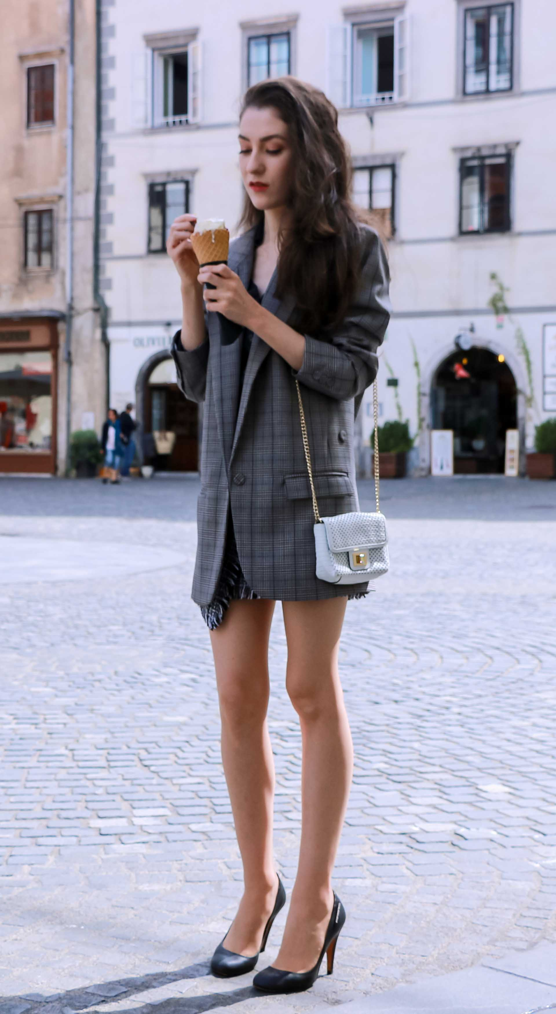 Fashion Blogger Veronika Lipar of Brunette from Wall Street dressed in Erika Cavallini oversized boyfriend checked blazer with short tweed black and white mini skirt from streets, black pumps and white chain strap shoulder bag while standing down the street in Ljubljana with ice cream in her hand