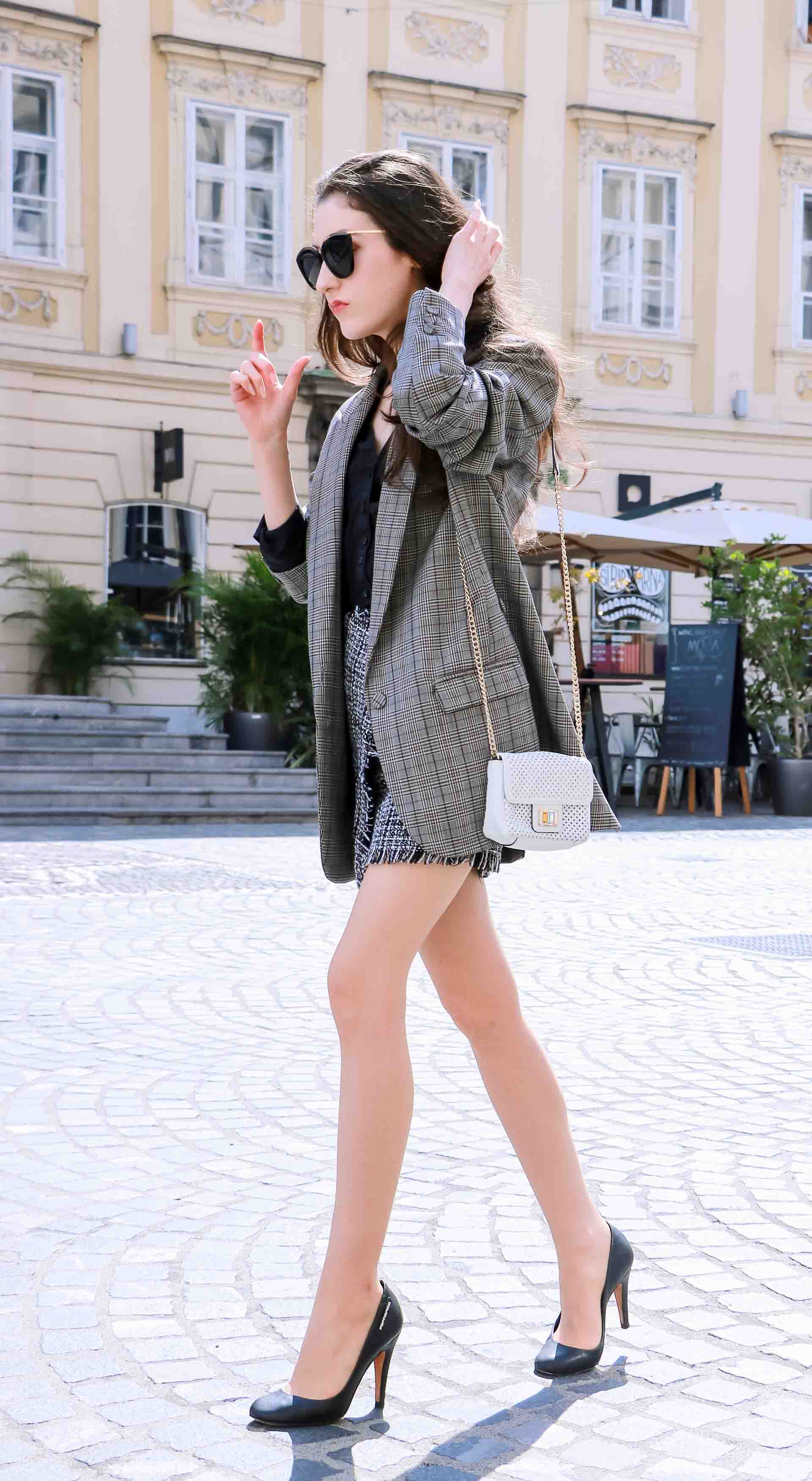 Fashion Blogger Veronika Lipar of Brunette from Wall Street dressed in Erika Cavallini oversized boyfriend plaid blazer with short tweed black and white mini skirt from streets, black pumps and white chain strap shoulder bag while dancing on the street in Ljubljana