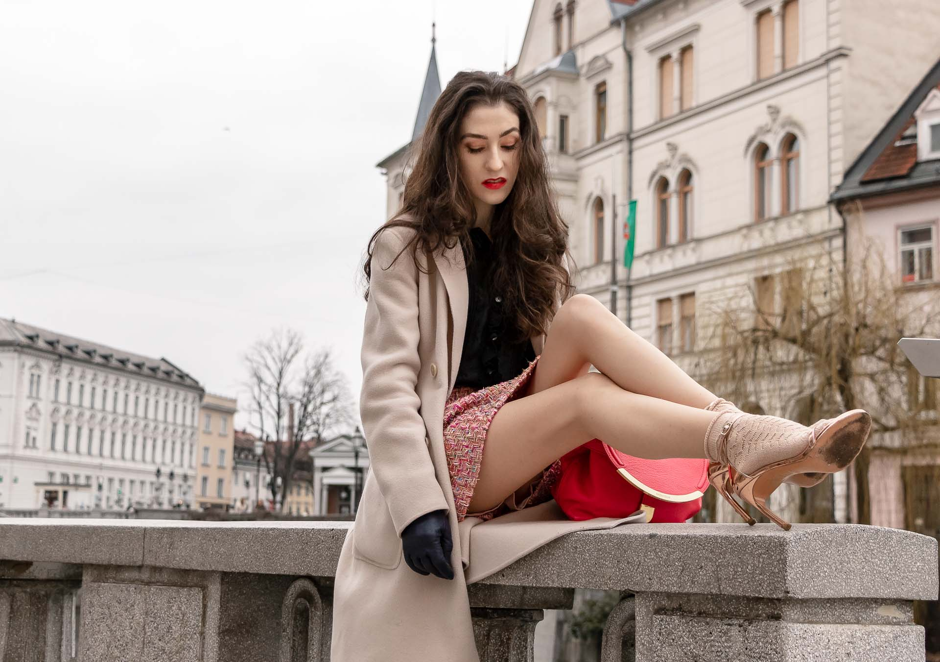 Fashion Blogger Veronika Lipar of Brunette from Wall Street dressed in bronze socks and high shine rose gold Songnudist sandals from Stuart Weitzman, tweed Storets minis skirt, black blouse, off white Weekend Maxmara coat while sitting on the wall in Ljubljana