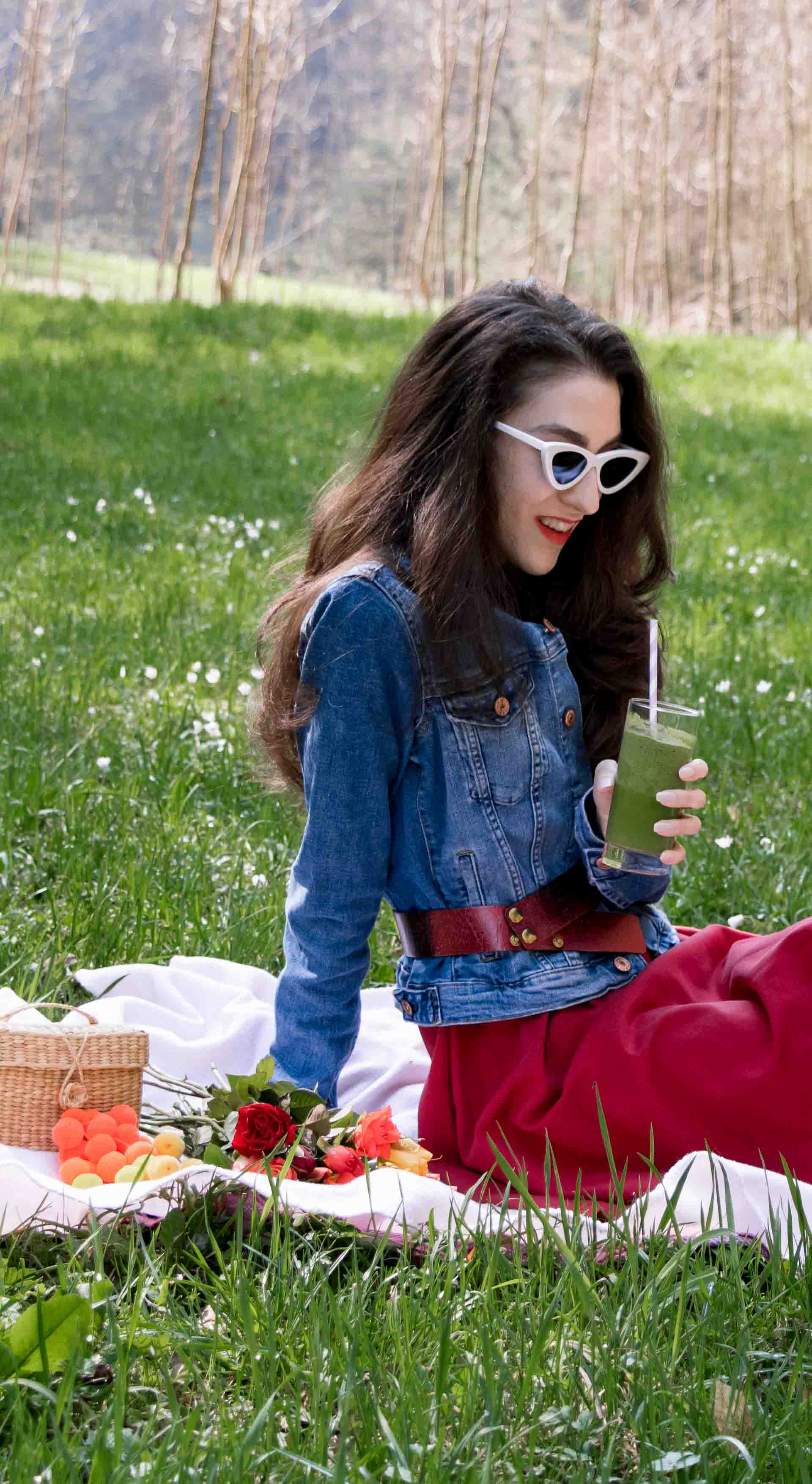 Veronika Lipar Fashion Blogger of Brunette from Wall Street wearing red dress, dangling belt, blue denim jacket, white socks and white pumps, Sam Eldeman x Le Specs, white lolita cat-eye sunglasses, Nannacay raffia basket bag while drinking smoothie on the pink picnic blanket