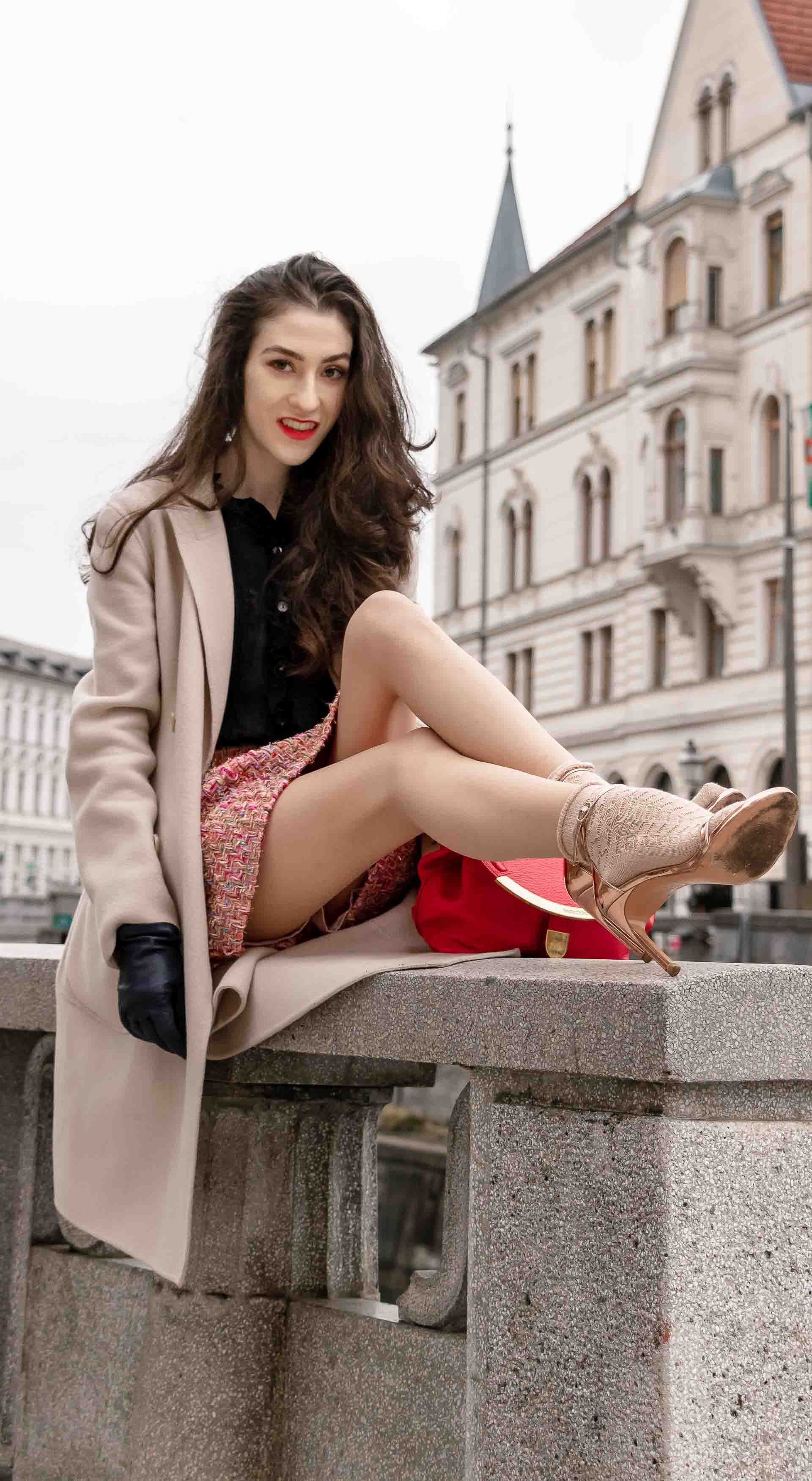 Fashion Blogger Veronika Lipar of Brunette from Wall Street dressed in bronze socks and sandals from Stuart Weitzman, tweed Storets mini skirt, black blouse, off white Weekend Maxmara coat while sitting on the wall in Ljubljana