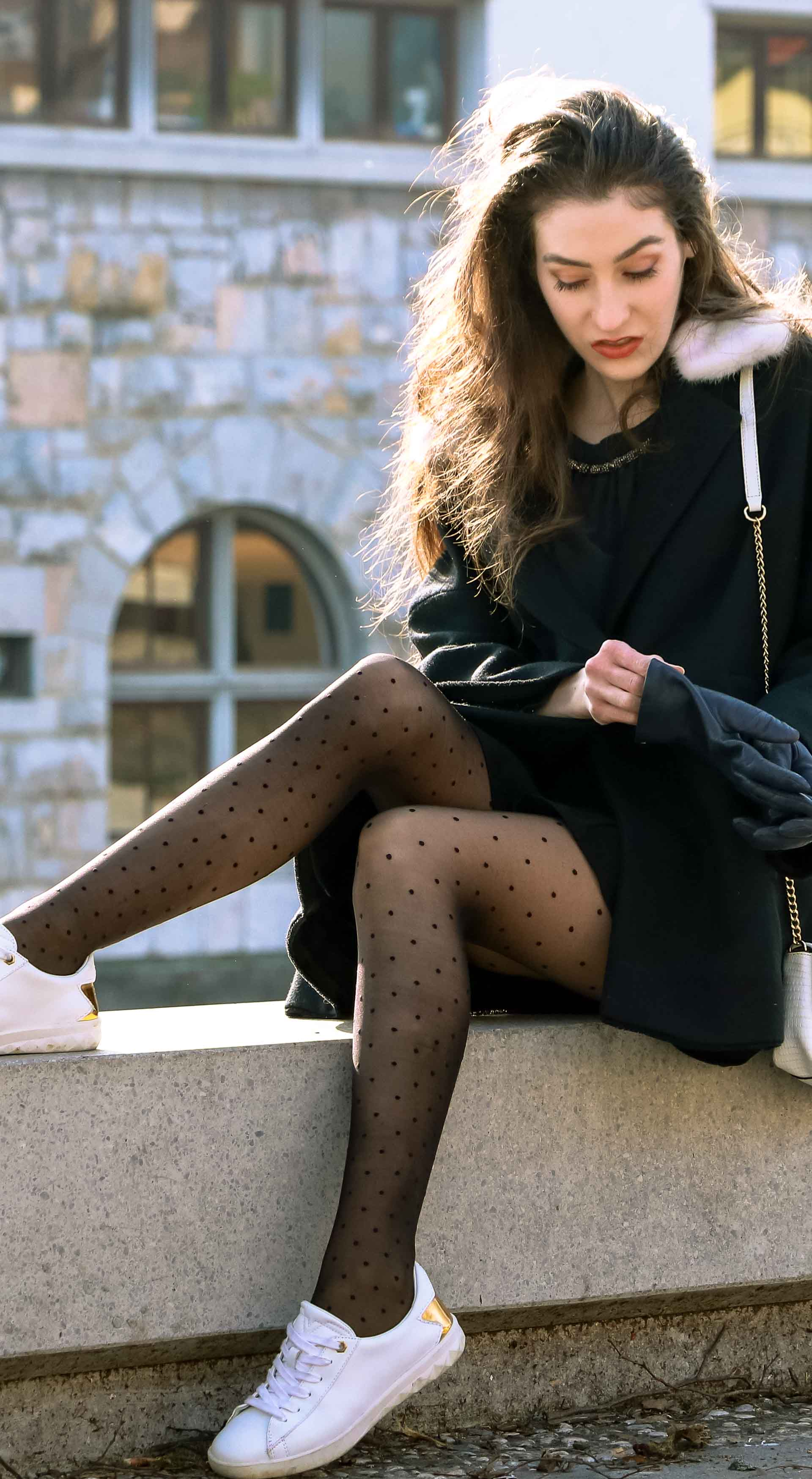 Fashion Blogger Veronika Lipar of Brunette from Wall Street dressed in a black Escada cape, black mini skirt and white sneakers from Diesel with black polka dot tights and white shoulder chain bag and blue leather gloves while sitting on a wall