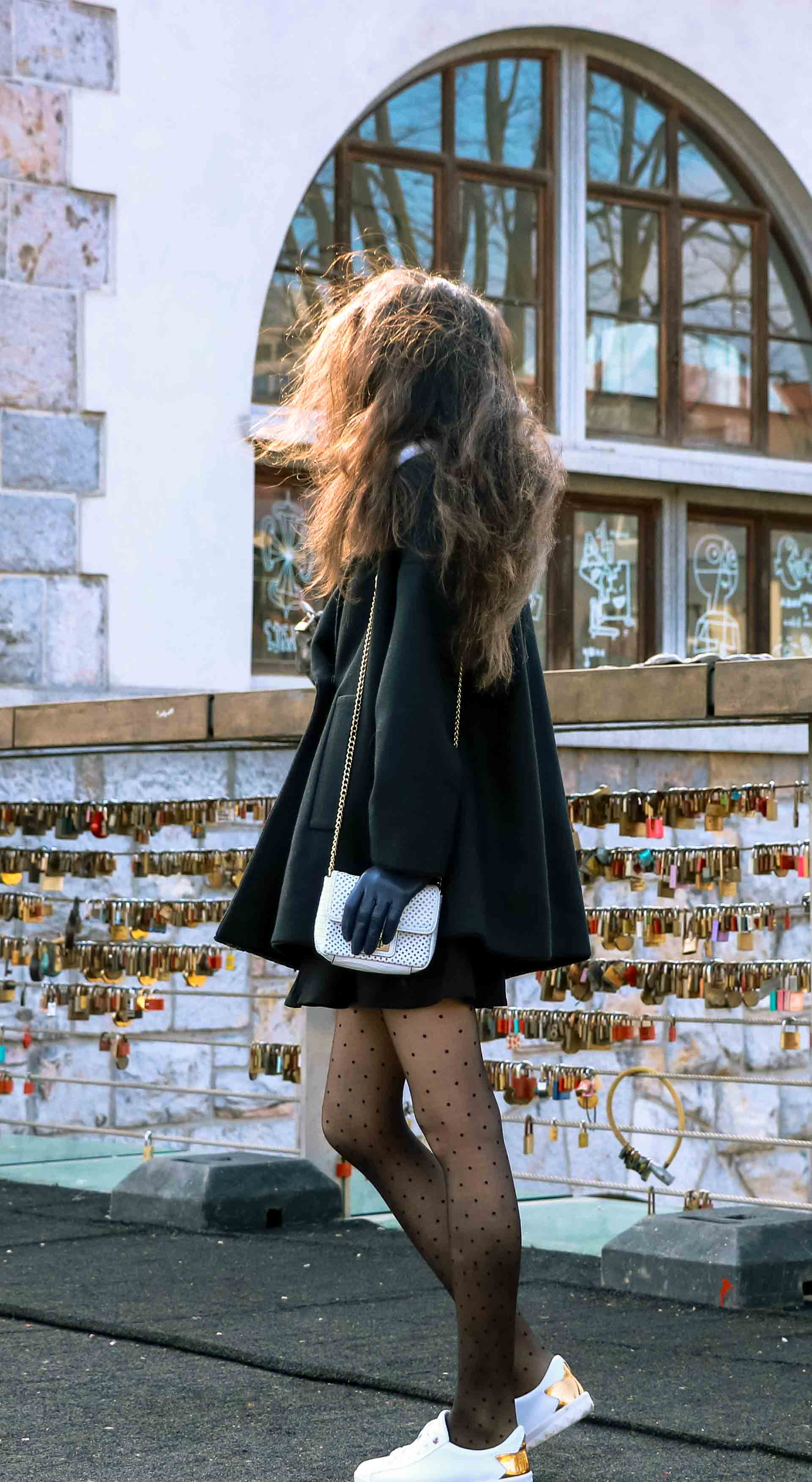 Fashion Blogger Veronika Lipar of Brunette from Wall Street wearing black Escada cape, black mini skirt and white sneakers from Diesel with black polka dot tights and white shoulder chain bag and blue leather gloves while standing on a chain bridge