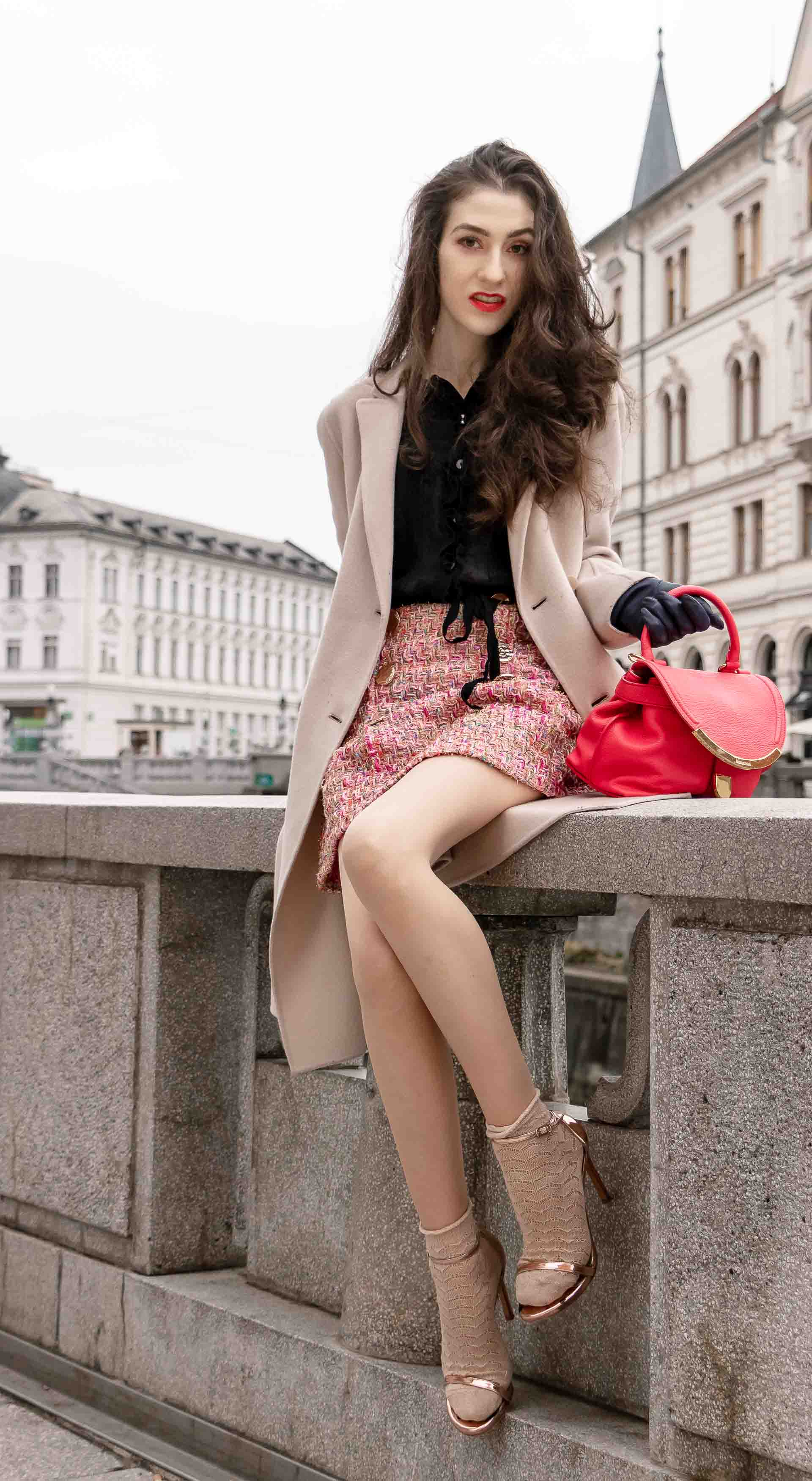 Fashion Blogger Veronika Lipar of Brunette from Wall Street dressed in bronze socks and sandals from Stuart Weitzman, tweed Storets mini skirt, black blouse, off white Weekend Maxmara coat getting up after sitting on the wall in Ljubljana