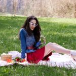 Veronika Lipar Fashion Blogger of Brunette from Wall Street dressed in red dress, dangling belt, blue denim jacket, white socks and white pumps, white lolita cat-eye sunglasses from Le Specs, Nannacay raffia basket bag while sitting on the pink picnic blanket