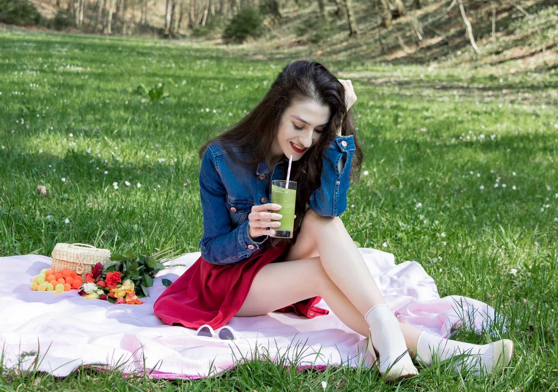 Veronika Lipar Fashion Blogger of Brunette from Wall Street wearing red dress, dangling belt, blue denim jacket, white socks and white pumps, Sam Eldeman x Le Specs, white lolita cat-eye sunglasses, Nannacay raffia basket bag while holding green smoothie on the pink picnic blanket
