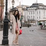 Fashion Blogger Veronika Lipar of Brunette from Wall Street wearing bronze socks and sandals from Stuart Weitzman, tweed Storets minis skirt, black blouse, off white Weekend Maxmara coat while leaning on the city lamp in Ljubljana