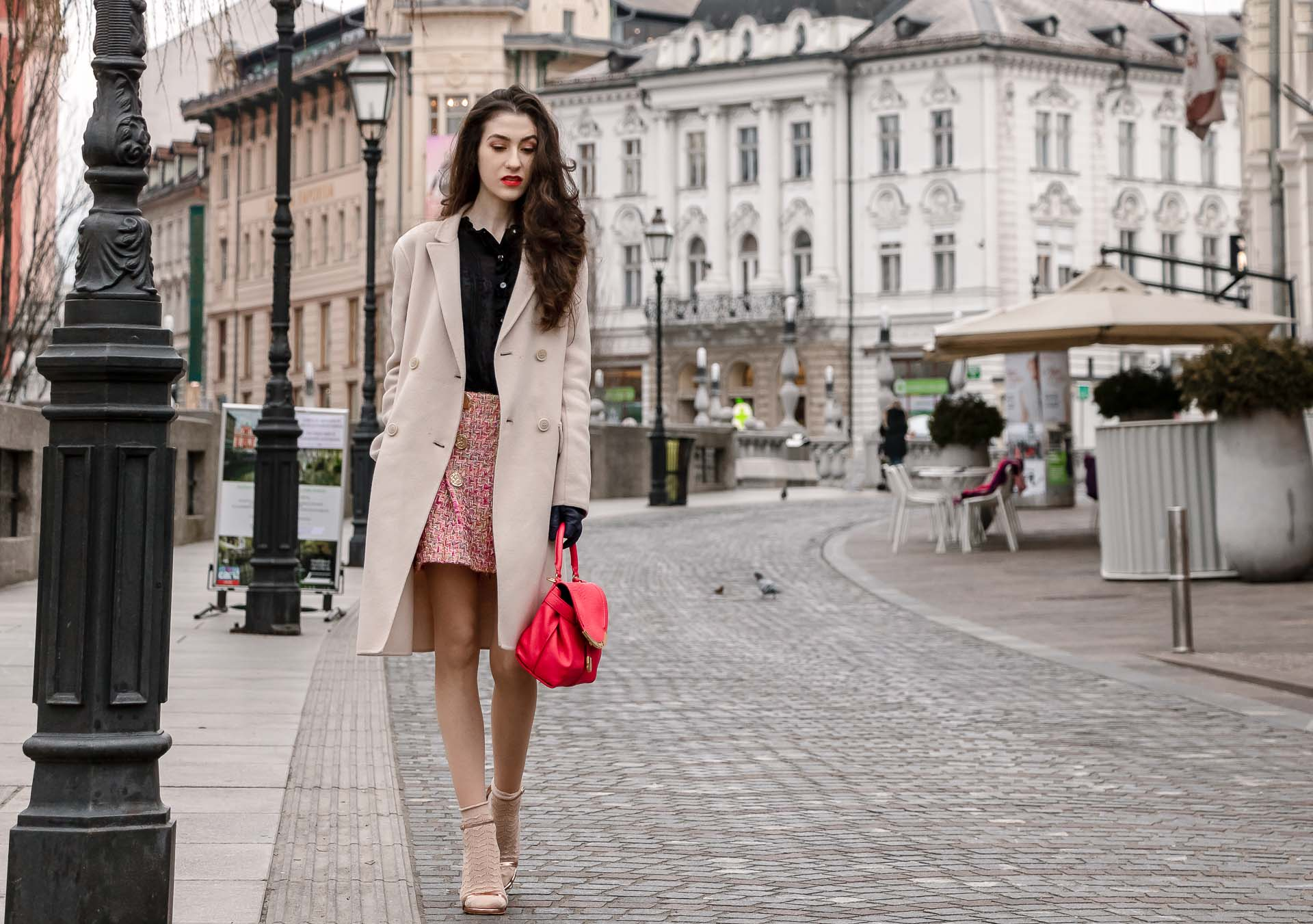 Fashion Blogger Veronika Lipar of Brunette from Wall Street wearing bronze socks and sandals from Stuart Weitzman, tweed Storets minis skirt, black blouse, off white Weekend Maxmara coat while walking down the street in Ljubljana