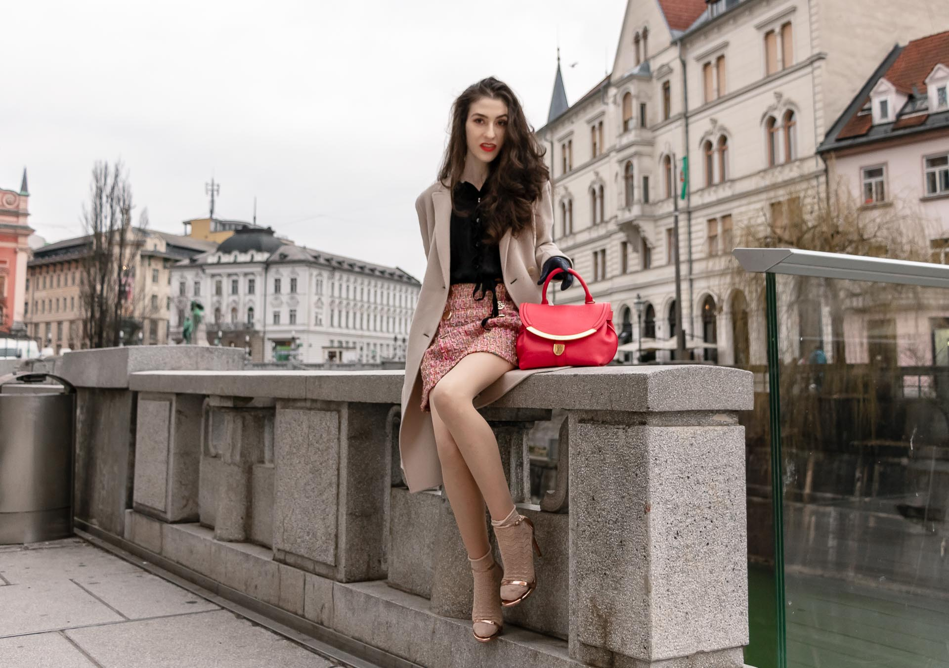 Fashion Blogger Veronika Lipar of Brunette from Wall Street wearing bronze socks and sandals from Stuart Weitzman, tweed Storets mini skirt, black blouse, off white Weekend Maxmara coat getting up after sitting on the wall in Ljubljana