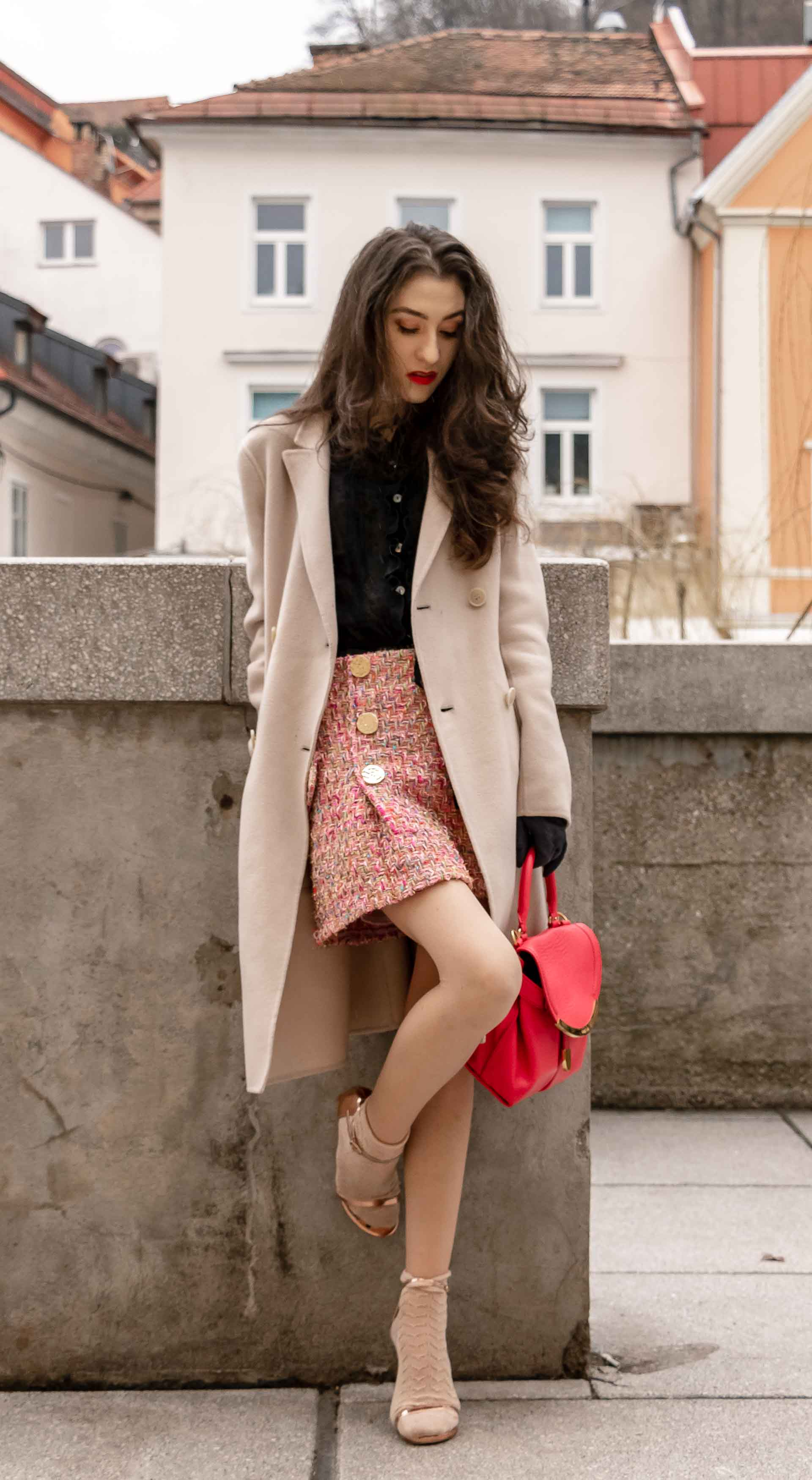 Fashion Blogger Veronika Lipar of Brunette from Wall Street wearing bronze socks and sandals from Stuart Weitzman, tweed Storets minis skirt, black blouse, off white Weekend Maxmara coat while leaning on the wall in Ljubljana