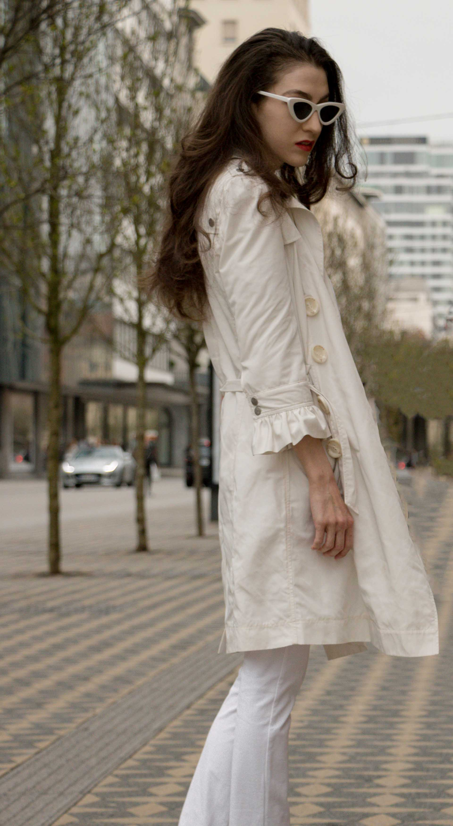 Veronika Lipar Fashion Blogger of Brunette from Wall Street wearing all in white suit from Juicy Couture, long white trench coat with ruffled sleeves, Adam Selman x Lespecs white lolita sunglasses while standing on the Slovenska cesta street in Ljubljana