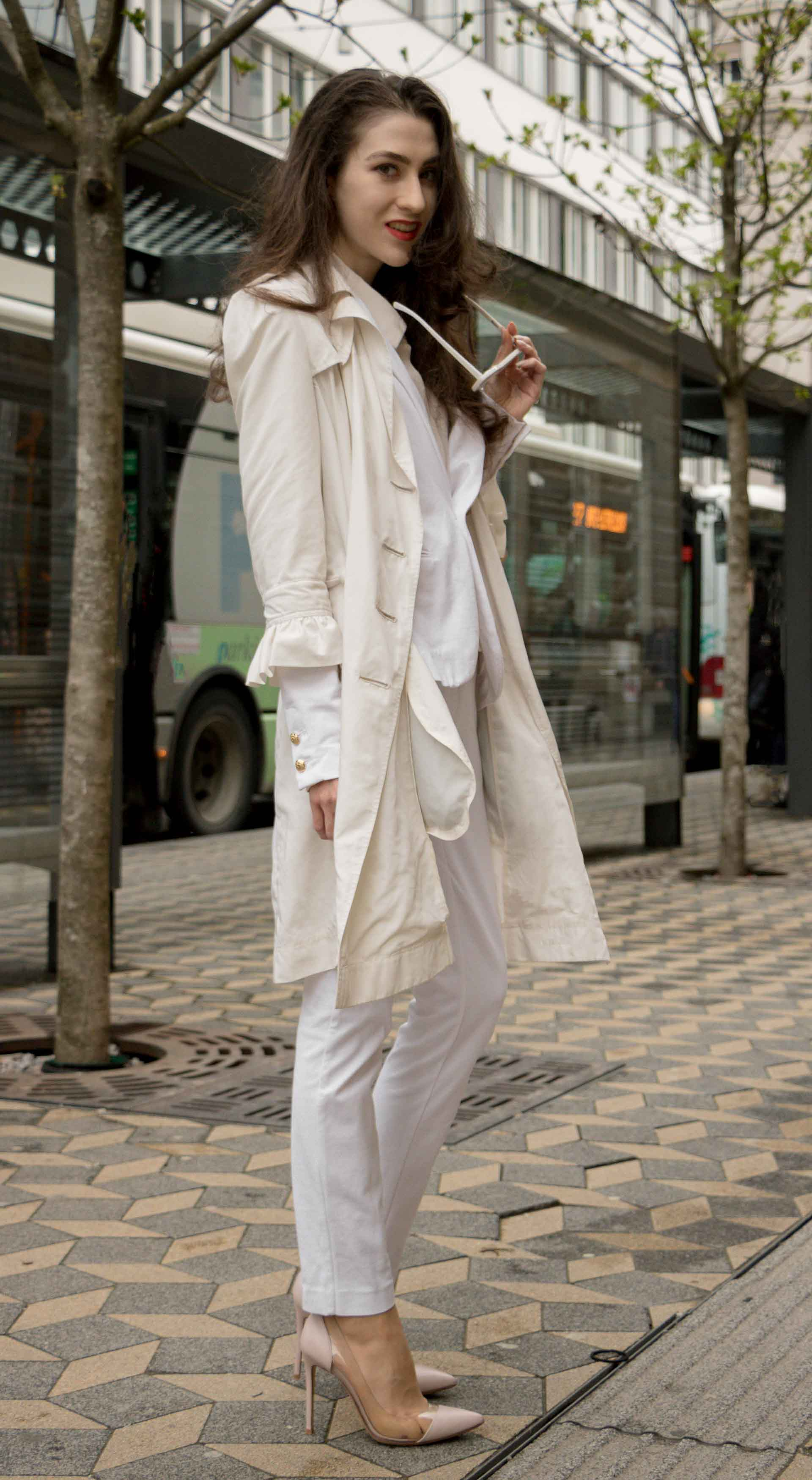 Veronika Lipar Fashion Blogger of Brunette from Wall Street dressed in formal business white suit from Juicy Couture, long white trench coat with ruffled sleeves, Adam Selman x Lespecs white lolita sunglasses, blush Gianvito Rossi plexi pumps for work in spring summer
