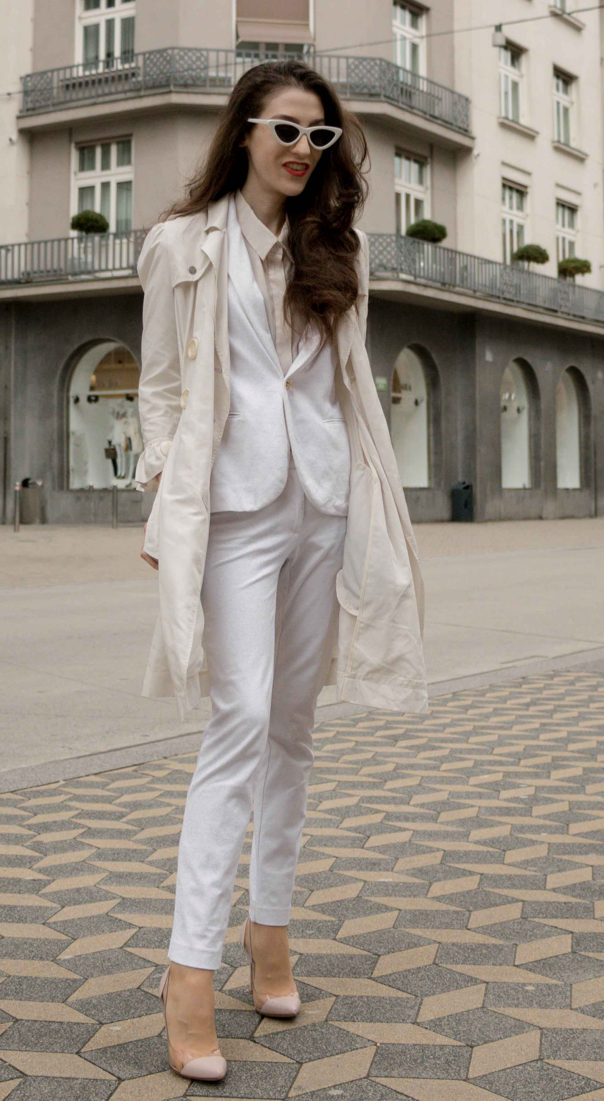Veronika Lipar Fashion Blogger of Brunette from Wall Street dressed in formal business white suit from Juicy Couture, long white trench coat with ruffled sleeves, Adam Selman x Lespecs white lolita sunglasses, blush Gianvito Rossi plexi pumps while standing on the Slovenska cesta street in Ljubljana