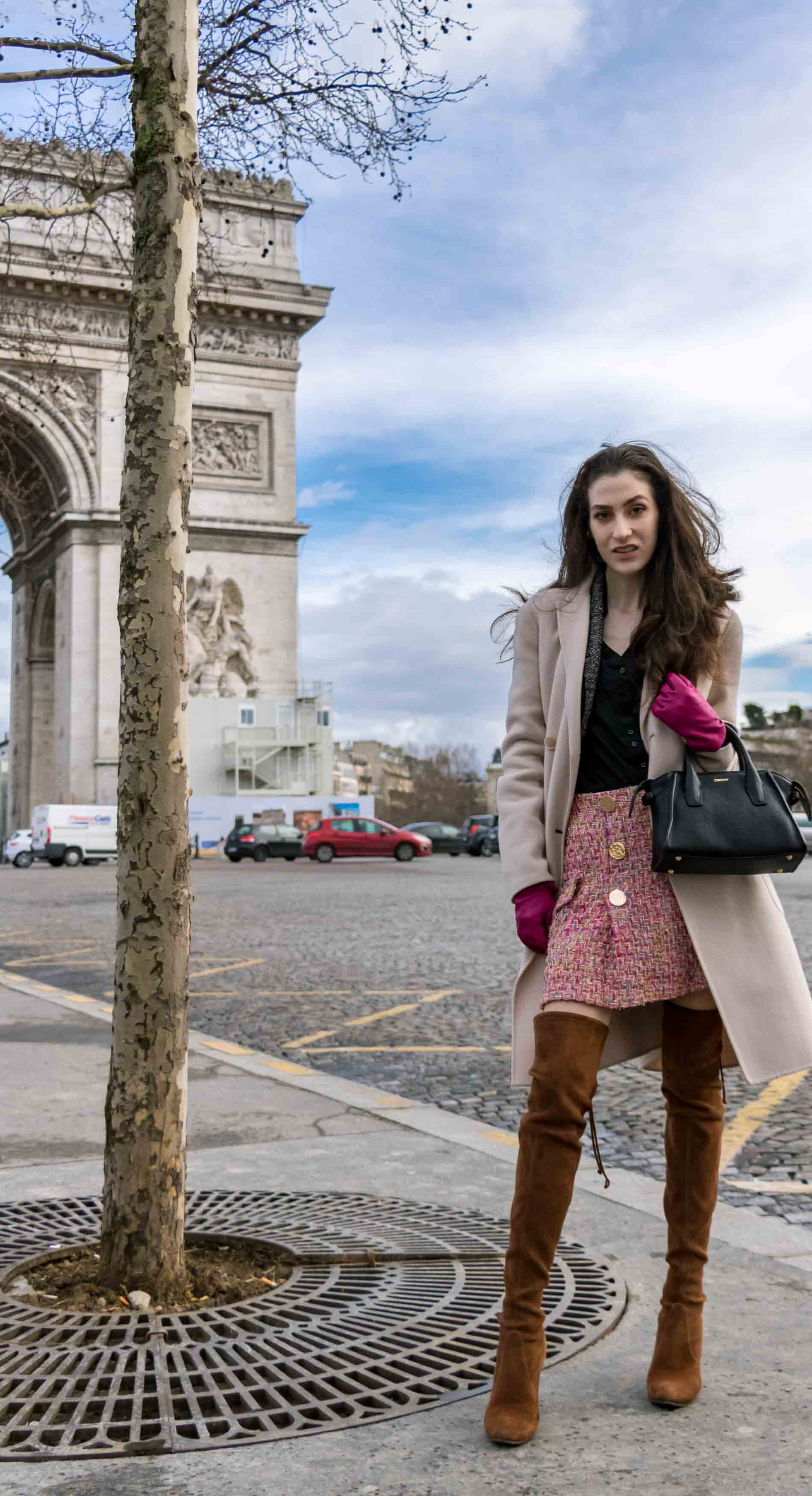 Fashion Blogger Veronika Lipar of Brunette from Wall Street dressed in Stuart Weitzman over the knee boots, Weekend Maxmara coat, Storets pink tweed shorts, black shirt, pink leather gloves and black small bag during Paris fashion week autumn winter 2018/19 standing infant of the Arc du Triomphe