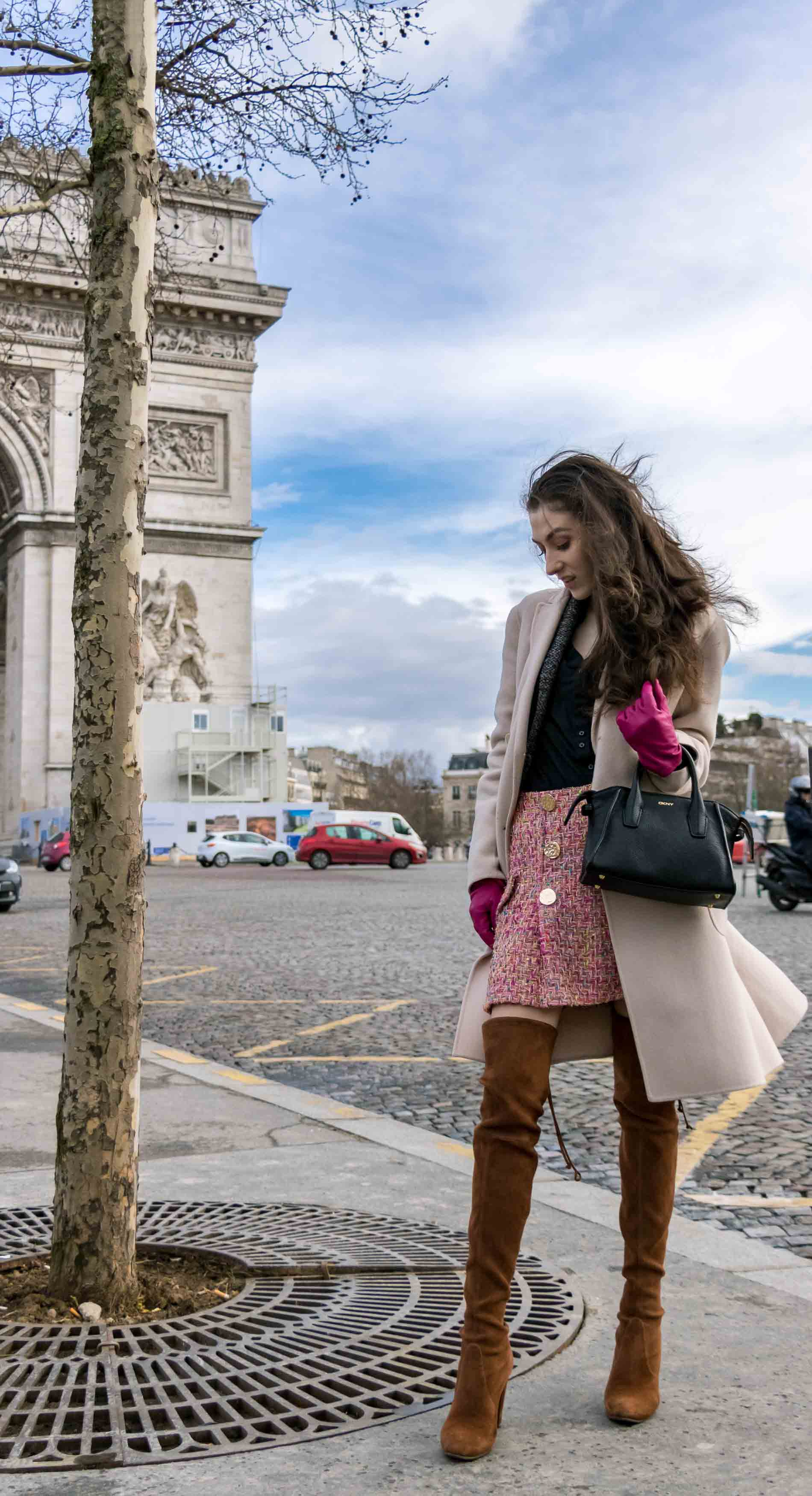 Fashion Blogger Veronika Lipar of Brunette from Wall Street wearing in Stuart Weitzman o tkboots, Weekend Maxmara coat, Storets pink tweed shorts, black shirt, pink leather gloves and black small bag during Paris fashion week autumn winter 2018/19 standing infant of the Arc du Triomphe