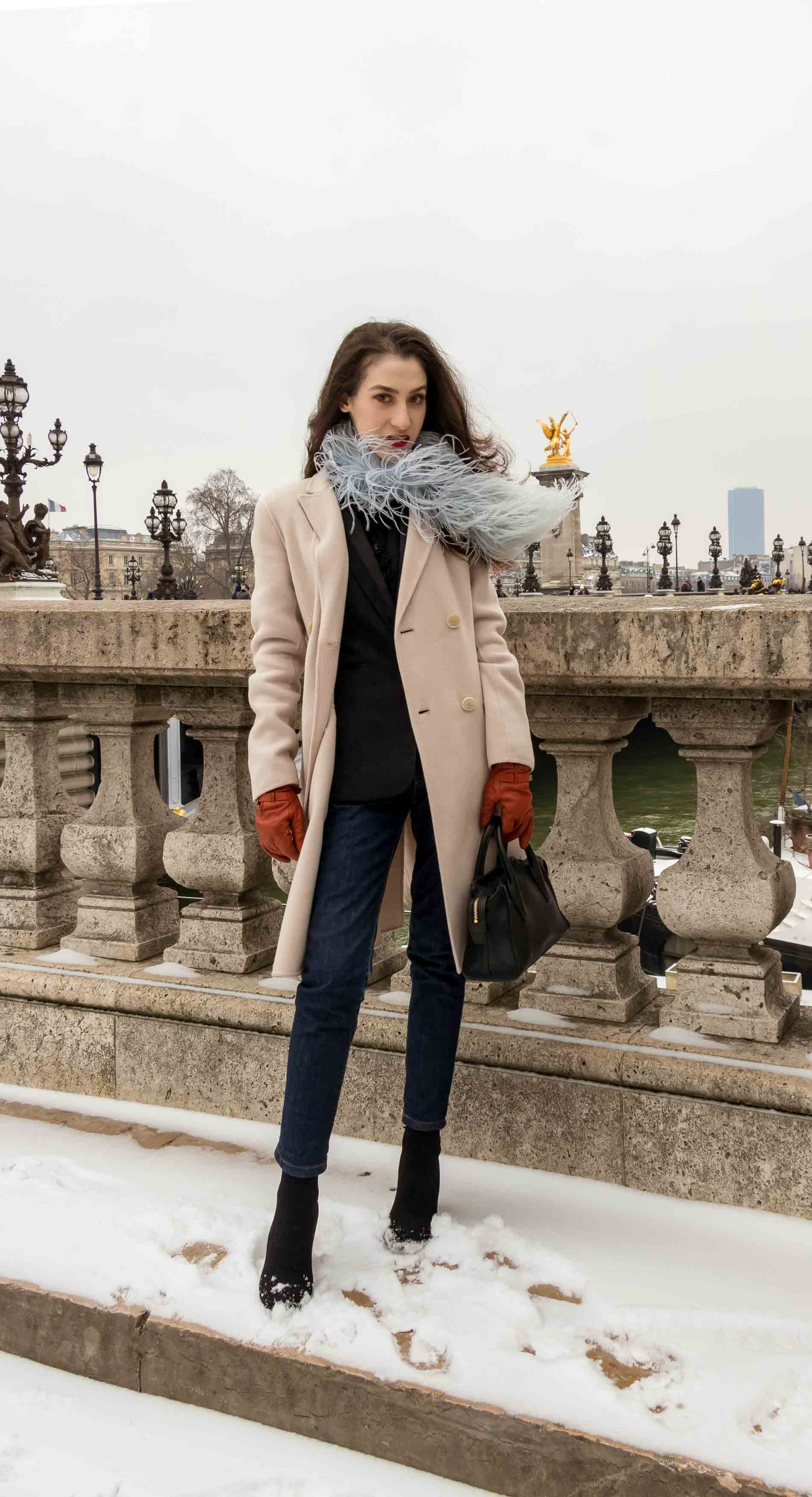 Fashion Blogger Veronika Lipar of Brunette from Wall Street wearing feathers, Weekend Maxmara coat, dark denim jeans, black sock boots, leather gloves, standing at Pont du Alexandre III in Paris during Paris fashion week fall winter 2018/19