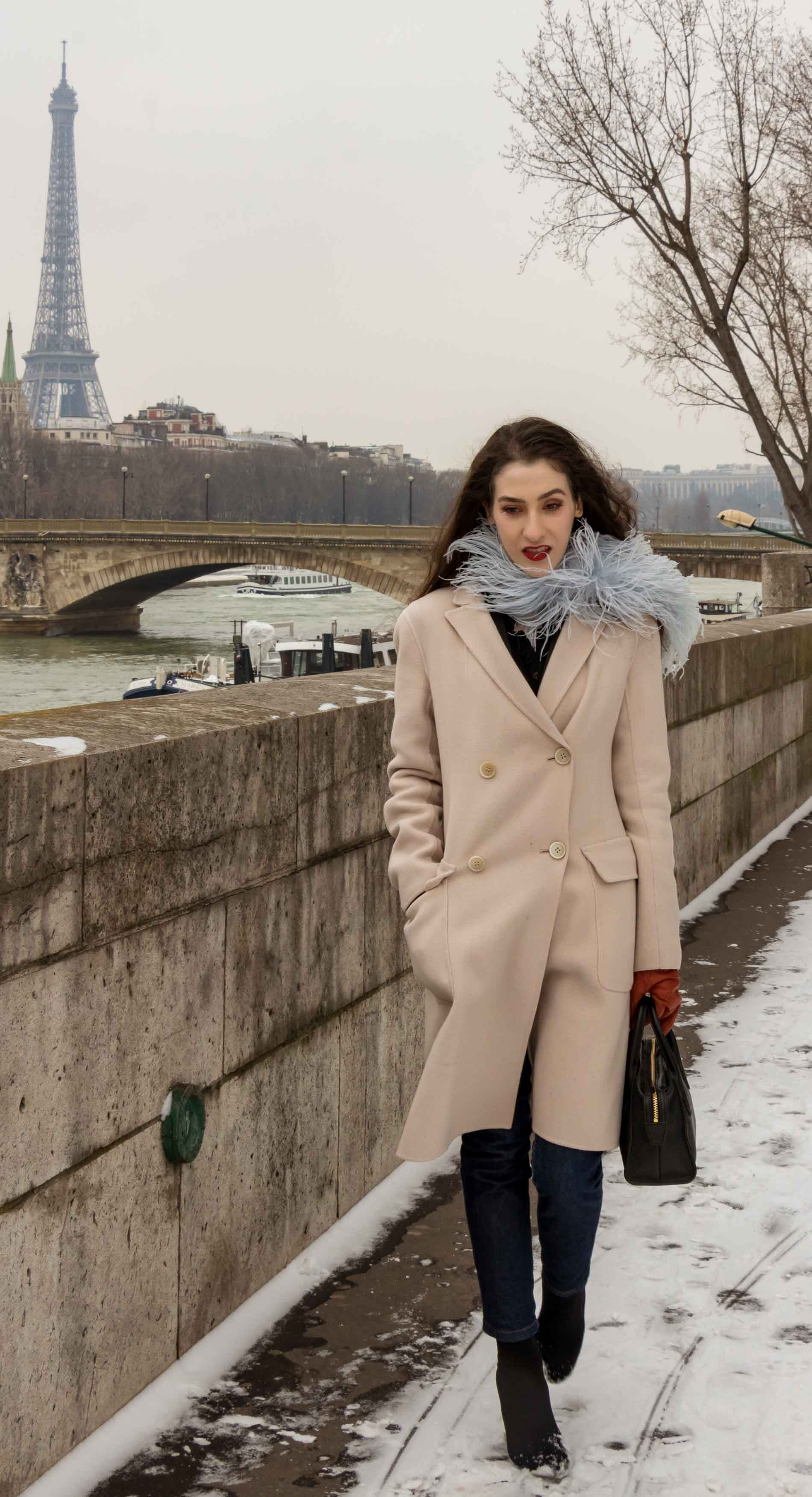 Fashion Blogger Veronika Lipar of Brunette from Wall Street wearing feathers, Weekend Maxmara coat, dark denim jeans, black sock boots, leather gloves, standing at Pont du Alexandre III in Paris during Paris fashion week autumn winter 2018/19